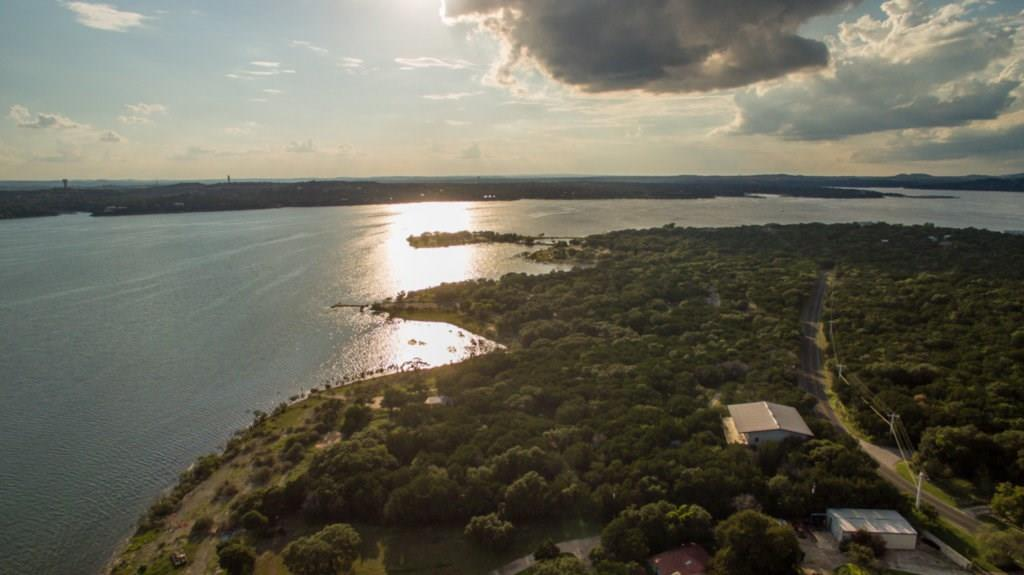 Nestled between an empty lot & Windy Point Park, this 5.8 acre lot with 227 feet of waterfront on main basin of Lake Travis faces SW towards Mansfield Dam. There is a 10,000+/- sf 2-story metal structure with living quarters and garages next to the street. There is also a 1,200+/- square foot cabin midway to the water which is grandfathered. Property is fenced, gated and heavily treed with a volleyball court and concrete boat ramp allowing recreational water access. Great opportunity for a single family development, luxury lakefront condominiums, a corporate retreat, a family compound or a spectacular lake estate!