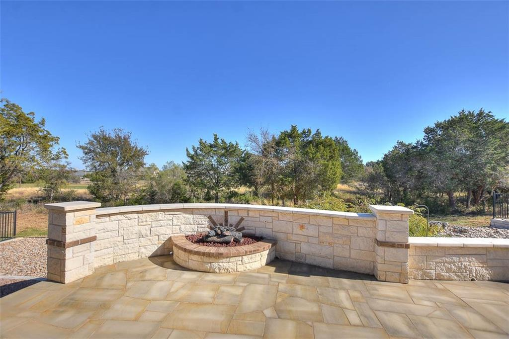A stone Patio with seat wall overlooks winding Cowan Creek Golf Course at this Sun City Texas Morningside Lane Estate Home.  Drought-resistant landscaping circles the home with pride, forming a lock & leave exterior for those who love travel.  Inside, a wide Split Foyer offers a tiled Formal Dining with Butler's Pantry on one side, while on the other side, French doors reveal the Study/Computer Room. All of the front windows are treated with stained plantation shutters adding rich, yet cozy, appeal.  Traditional white plantation shutters treat the remaining windows. As usual the Kitchen is the heart of the home, but never more so than in this home, where the Kitchen is a true hub with its generous granite counter space, plentiful cabinets, and shimmering stainless appliances.  The nearby Walk-In Pantry is like having your own little H.E.B.  Yet another sink and works space is provided in the Over-sized Garage, where a nifty workshop area and useful storage are form great use of space.  Two Guest Bedrooms are nicely separated from the Primary Bedroom, adding privacy for all.  The larger of the two Guest Bedrooms has been divided into two areas, sleeping and living, also useful for an Office-at-Home. The two Guest Bedrooms flank a nice Guest Bath.  A stone gas-log Fireplace anchors the Great Room, where plenty of space is provided for a casual Dining area, or game table. Quietly-separated from the Two Guest Bedrooms, the Primary Bedroom boasts a crowned tray ceiling, while a trio of shuttered windows frame Cowan Creek Golf Course views.  Meanwhile, the en suite Bath hosts a jumbo Walk-In Shower, dual vanities, Two Linen Closets, and a generous Walk-In Closet. Off the Great Room, a Screened Porch opens to the before-mentioned Stone Patio with gas fire pit.  No extra charge for the big Texas sky; just bring your own telescope!