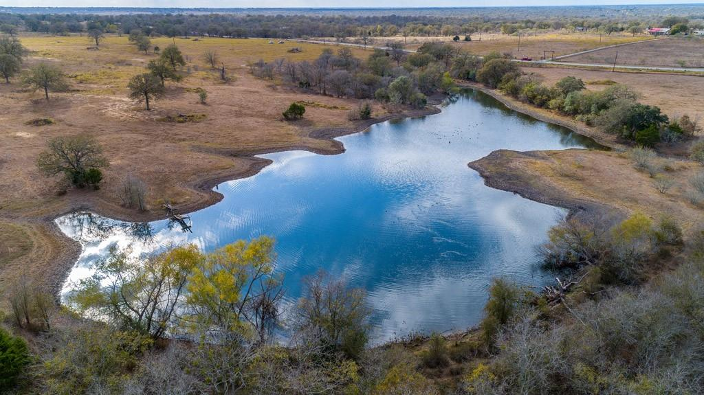 """11.57 acres to be surveyed out of 2 larger tracts. New development on FM 86 just off of Hwy 20 in Bastrop County between Bastrop and Lockhart, TX. Beautiful, expansive stock pond, mature trees, sunshine and big beautiful skies where you can really see the stars of Texas at night. This incredible land tract was to be part of a new subdivision called Blue Sky Estates, estimated to be finalized in March of 2021, but could close as a separate tract now. Great property for those who want to """"Get outta' town"""" but not too far out, where you can have your chickens, goats and can even bring your horse. Restricted to site built homes of 1200+ SF, including barndominiums, but no manufactured, mobile or modular homes are allowed. Convenient to Historical Bastrop, TX with great shopping and fun things to do, Lockhart, TX, the Bar-B-Q Capital of Texas, with easy commutes to ABIA, COTA, Tesla and Austin, Texas. Your opportunity to be one of the first to enjoy this great new development. Also offered for sale with the adjacent 2.66 acres for additional road frontage. Water line on FM 86, buyer to determine if Aqua Water is available for this property or whether a well will be required.  Buyer will be responsible for all utilities. Taxes indicate the Ag exemption of the larger tracts."""