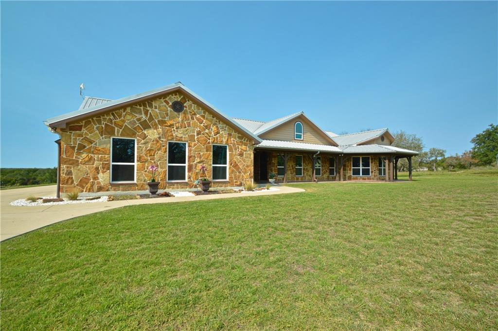 Peaceful country setting, beautiful stone home on 48 +- acres, only 45 minutes from Austin. This horse ranch is complete with a lighted roping or riding arena, 50' covered round pen, 3 loafing sheds with traps and auto water, a horse walker and a horse conditioning rehab pool.  Ranch has a large horse barn (40' x 80') with 8 stalls, tack area and a horse stock.  A 75' x 40' Equipment barn, 26' x 50' wood Hay barn, and a 18' x 24' carport.  Plenty of room to build a stud barn or add some cabins for guests or Air BnB.  Also, good hunting on the back part of the land which has plenty of cover for wildlife or use it for roping cattle, ag projects. 