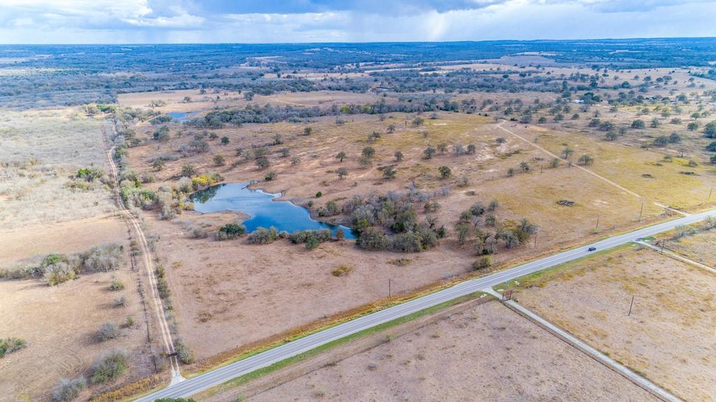 """14.22 acres to be surveyed out of 2 larger tracts. New development on FM 86 just off of Hwy 20 in Bastrop County between Bastrop and Lockhart, TX. Beautiful, expansive stock pond, mature trees, sunshine and big beautiful skies where you can really see the stars of Texas at night. This incredible land tract was to be part of a new subdivision called Blue Sky Estates, estimated to be finalized in March of 2021, but could close as a separate tract now. Great property for those who want to """"Get outta' town"""" but not too far out, where you can have your chickens, goats and can even bring your horse. Restricted to site built homes of 1200+ SF, including barndominiums, but no manufactured, mobile or modular homes are allowed. Convenient to Historical Bastrop, TX with great shopping and fun things to do, Lockhart, TX, the Bar-B-Q Capital of Texas, with easy commutes to ABIA, COTA, Tesla and Austin, Texas. Your opportunity to be one of the first to enjoy this great new development. Water line on FM 86, buyer to determine if Aqua Water is available for this property or whether a well will be required. Buyer will be responsible for all utilities. Taxes indicate the Ag exemption of the larger tracts."""