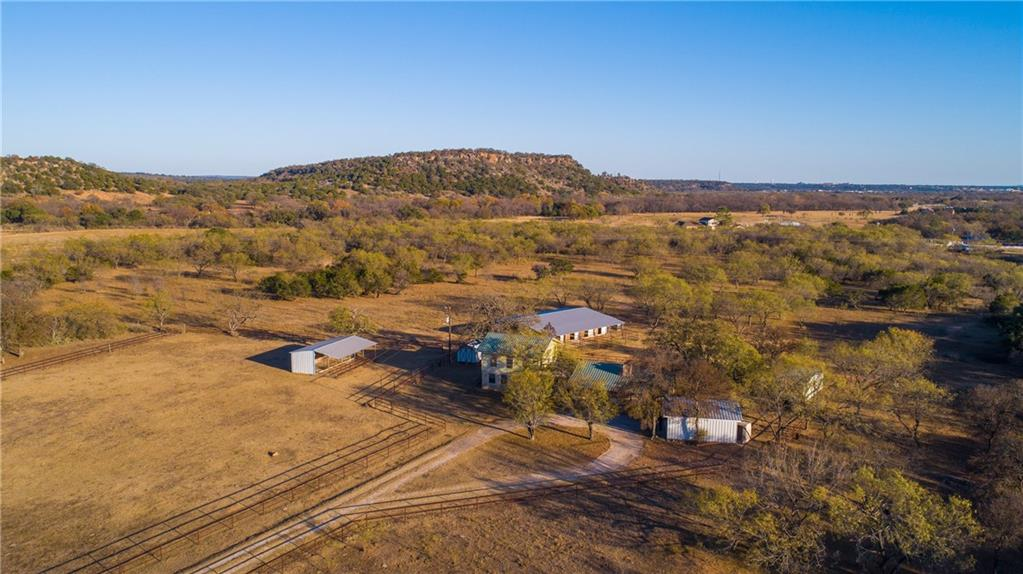 24.87-acre horse property is now available in the scenic area just 5 miles North and West of Marble Falls, TX.  This property includes a ~2484 sqft home, five stall horse barn, two storage buildings, loafing shed, horse fencing and a carport.   The house and 4.39 acres are located in Sparerib Estates with light restrictions and a $50/year POA road maintenance fee.  The remaining contiguous 20.48 acres is located in Tobyville Acres which has a slightly different set of restrictions.  The property is fenced and cross fenced, mostly with a horse friendly pipe fence with some slick wire in the back of the property. Sparerib Creek runs thru the southern edge of the property.   The grounds include several nice oak trees around the house, a water well and a recently updated septic system. •  Main House: Two story ~2484 sqft house built in 1985, three bedroom (two down and one up), two full baths, covered front and back porches, woodburning stove in the living room, brick fireplace in the master bedroom.  The house needs some finishing work and TLC.  •  Five stall horse barn with paddocks for each stall. •  Loafing shed. •  Carport for 2 vehicles. •  Completely fenced and cross fenced – horse friendly pipe fencing in front and slick wire in the back. Property nicely located ~5 miles North and West of Marble Falls, 54 miles to downtown Austin and 92 miles due North of San Antonio. Additional paved frontage on Fieldcrest rd.