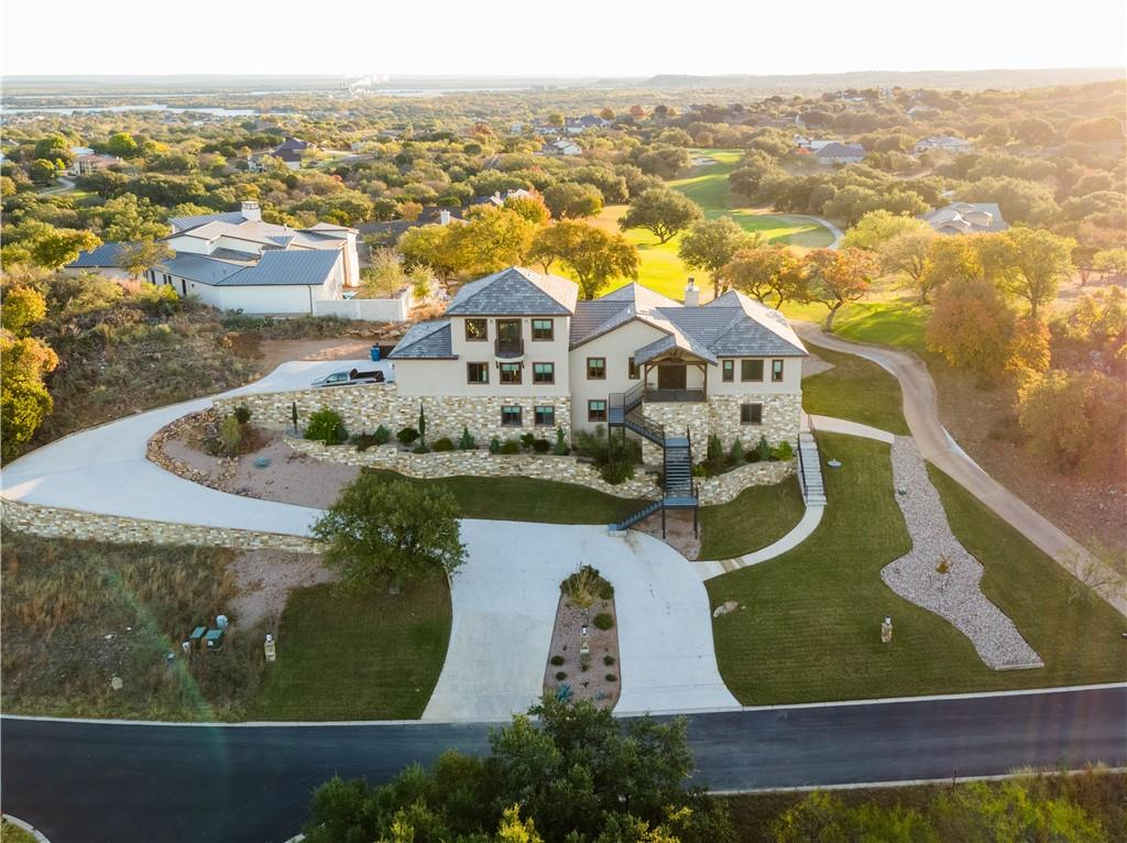 Majestic views of the Horseshoe Bay Apple Rock Golf Course and Packsaddle Mountain make this house an incredible place to call home. With over 5,000 square feet, there is plenty of room for both family and friends. With amazing spaces to entertain and enjoy the beautiful Texas Hill Country, this home boasts 4 decks, an outdoor fire pit, game room/gym, office, 2 laundry rooms, 4 bedrooms, and 4 1/2 bathrooms. The main floor includes the primary living room, kitchen, master bedroom and bath, plus 2 bedrooms and another full bath. Separate living quarters are available downstairs with a bedroom, bathroom, living area, and kitchen. Great for a mother-in-law or caretaker suite. A bonus room upstairs could be used as an additional bedroom. Details such as electric window shades, LED lighting, and cozy coffee.