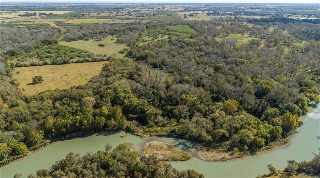 """A rare live water property in DeWitt County on the Guadalupe River! Located between Gonzales and Cuero, this unique property has over 1000' of river frontage with good access to the river.  The property is loaded with wildlife and has multiple habitat types with great plant diversity.  This diverse rolling 200 acres is about 85 % covered in trees with some open pasture and roadways being the balance.  There is also a large sand bar just in front of the landing providing a """"sometimes island"""" to utilize for recreation.  Furthermore, it is bordered to the East by McCoy Creek, another well traveled route for wildlife.  This is a top-notch hunting property with year-round hunting opportunities. The new owner will be """"ranch ready"""" with several items in good condition that convey with this gorgeous property.  Inside a fenced in yard, you will find a 36'x52' pavilion with concrete slab in place complete with electricity, RV hookups, water, septic, and firepit.  Located on a high point, this feature is great place to enjoy a cup of coffee in the morning while watching the wildlife or enjoy the fellowship of friends and family while you sit by the fire at night.  This pavilion provides protection for the 2015 Grand Design Solitude RV which will convey.  In addition, a two-seat 2012 John Deere Gator 825i and 2016 John Deere 5075E tractor with 250 hours including a front end bucket, shredder and grapple attachment will also stay. The several hunting stands and feeders will also be in place and ready to go.  The property is perimeter and cross fenced with the fencing being in good condition.   A portion of the property does lie within the 100-year floodplain. The property is currently qualified under the Agricultural tax valuation via a grazing lease and also has a Wildlife Management Plan in place."""