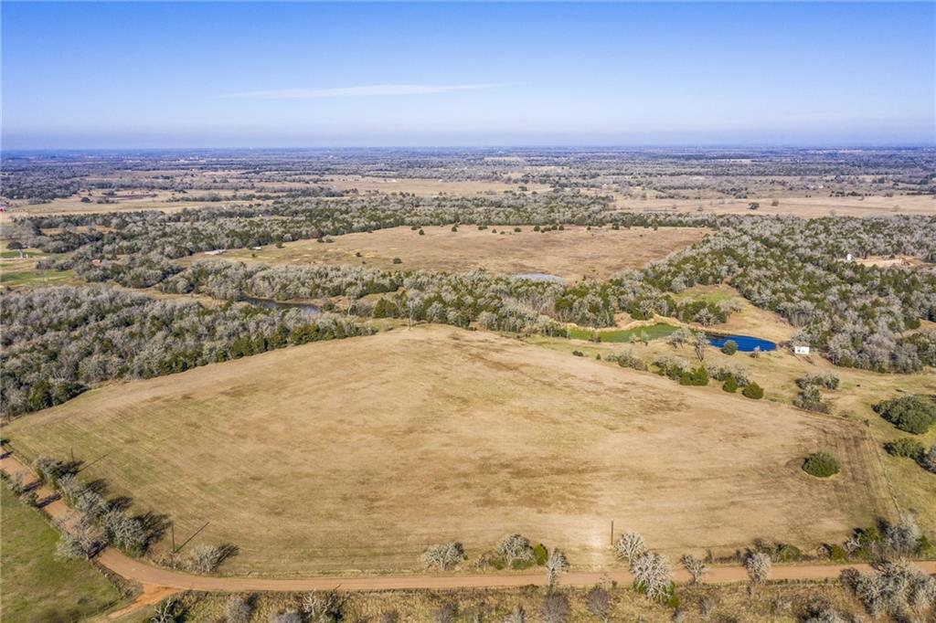 If you have been looking for beautiful ranch property close to town, then take a look at this unrestricted property only 8 minutes from Round Top and in Round Top ISD! 50+ acres at back of property w/lush coastal Bermuda grass makes perfect recipe for grazing cattle or horses. 20 acres currently fenced from cattle. Dedicated coastal hay field at front of property on Lange Rd, rendering approx. 80-100 bales in just 1 yearly cutting. 2 large stocked ponds for fishing. Woods w/trails separate front & back clearings… perfect for hunting. Perimeter fencing & cross fencing in place & electric fencing to deter cattle from visiting neighbors. Electric fencing (w/charger) extends to property boundary lines except in front hay field southside/Lange Rd, where mainly buffer fencing is used. Property has approx 2,400 ft rd frontage on Lange Rd w/Ledbetter waterline available. 2 metal carports, electric & water well in place. Beefmaster cattle, including bull & calves are negotiable along w/other property amenities.