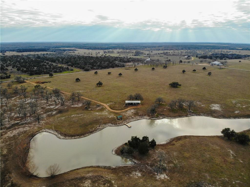 87.7 acres w/ALL utilities and covered RV site. An opportunity to own your Little Slice of Heaven in Texas! ~ Beautiful 87.7 acres with park-like setting, gorgeous post oaks, pasture, a 3 acre lake with pier and boat shed. Only 45 minutes from the Austin Airport. There is plenty of space for building your dream home with unspoiled natural terrain, spectacular sunsets and a view of the pond. It is the perfect combination of country, not too far from the big city. Deer and turkey have been seen roaming the land. AG Exemption currently in place for cattle. The property is currently being used for a small cattle operation but due to its size and location it could be an ideal property for investment or development. Utilities at the road. Build your custom home here. Property is fully fenced & cross-fenced with multiple gate entry. Great land to enjoy now, camping, R/V, horses, build your dream home/log cabin or simply hold for an investment as prices have been going up every year. Easy access to Highway 71 or I-10. It has paved road frontage on two sides which makes it easily divisible. Several nice building spots are available. Not in the flood zone. Across the road there is an additional 65 acres available with a 3 acre pond.
