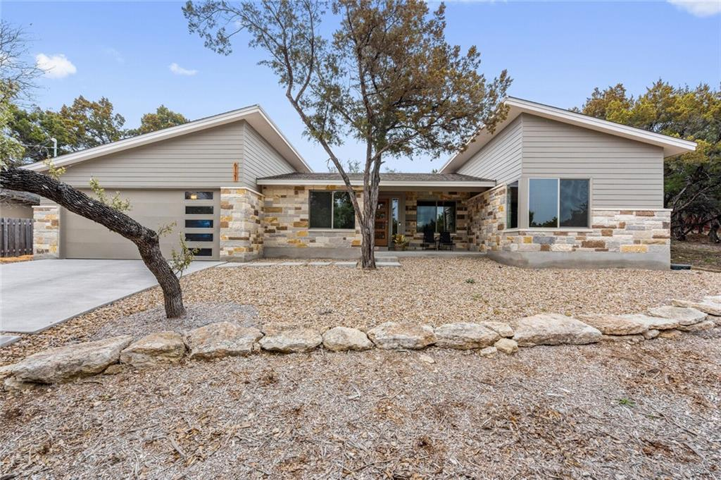 Set away from the roadway is this modern, three-bedroom, two-bath home located in Lago Vista built-in 2018. The front exterior has masonry trim and a Xeriscape lawn. Walk-in and be greeted with the living room equipped with built-in bookshelves, a fireplace, and multiple windows that allow ample light in. The spacious kitchen features Stainless Steel appliances, granite countertops, a gas stove, tile backsplash, a farmhouse sink, and bartop seating at the island. Adjacent to the kitchen, you will find the dining nook. This area is surrounded with large windows making every meal a scenic view. Laminate wood-like floors span the entire house. A sliding glass door leads to the backyard with a covered patio with a perfect view of the grove of trees on the property. The master bedroom has high ceilings and adorns a chic light fixture. The attached bathroom has a large walk-in shower, separate tub, and a walk-in closet with built-in shelves. Located only a mile away from the lake and in the highly rated Lago Vista ISD!