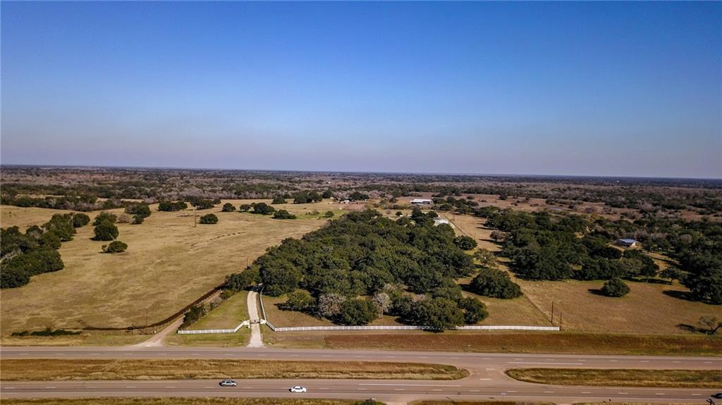 """Located ~9 miles southeast of Cuero and ~15 miles northwest of Victoria, this 16.71 acre horse farm is stunning in every sense of the word! As you pull off highway 87 and through the electric gate, you are greeted by lush green pastures, native wildlife, and gorgeous live oaks too abundant to countMeandering down the quarter mile driveway you will arrive at a beautiful 4,595 sqft brick home tucked away from the highway and offering great privacy and seclusion. Located behind the house is 3,040 sqft car garage/mancave  tastefully designed and complete with high-end finishes that is the ideal entertaining space sure to """"wow"""" any guest. Rounding out the property's improvements is a 720 sqft equipment shed, 4,400 sqft """"BarnMaster"""" 5 stall horse barn complemented by a 150 x100 riding arena both designed by, and for, horse lovers. This stunning property is being brought to market by its original owners who have meticulously cared for and managed every detail throughout. This offering is a can't miss opportunity for the buyer seeking a turnkey luxury property in the country, while providing close proximity to all amenities."""