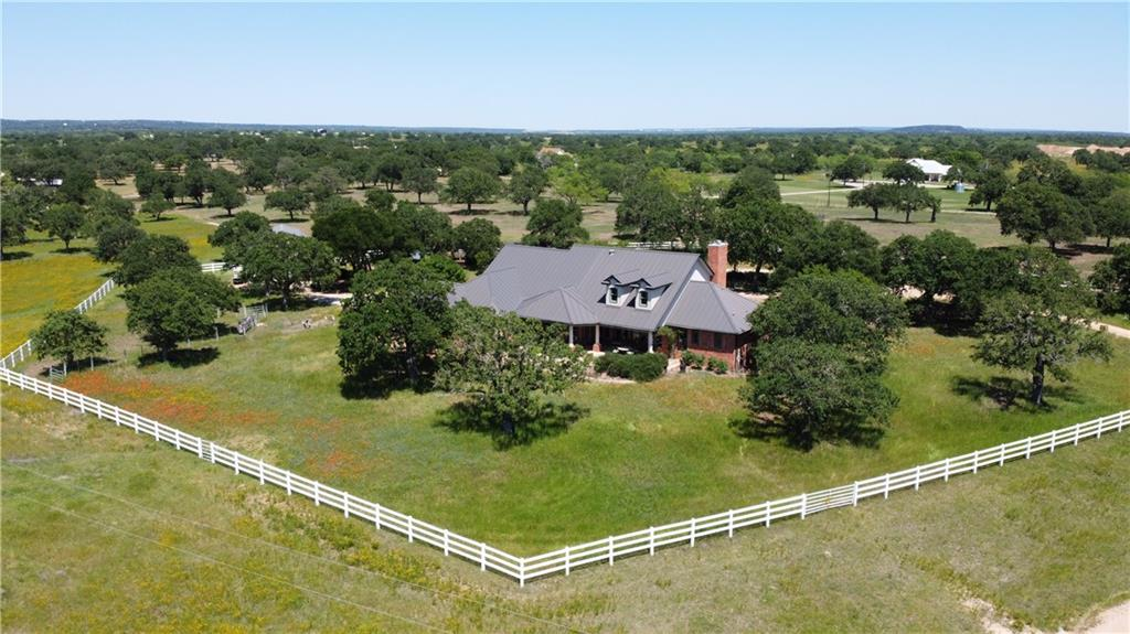 A beautiful custom home sitting on 50 acres of prime Texas Hill Country land, conveniently located near the Highland Lakes. The current owner has agriculture tax valuation, raises genuine Texas Longhorns and maintains other livestock and animals on the property. Much of the equipment and supplies will convey with sale. Livestock can also convey if desired. Entry from the road is through a large cedar beam archway with wrought iron gate. The house, approximately 3700 square feet with a walk-up, partially finished attic of 1300 square feet, is situated within a 2-acre fenced area. The remaining acreage is dedicated to pastures, wildlife, outbuildings and roads. Oak trees are abundant with most all areas cleared of mesquite and cactus. A small stock tank/pond is located near the back of the property. Approximately 21 acres of the land are used to grow and harvest coastal hay for livestock. Solid and well-maintained fences all around the property.