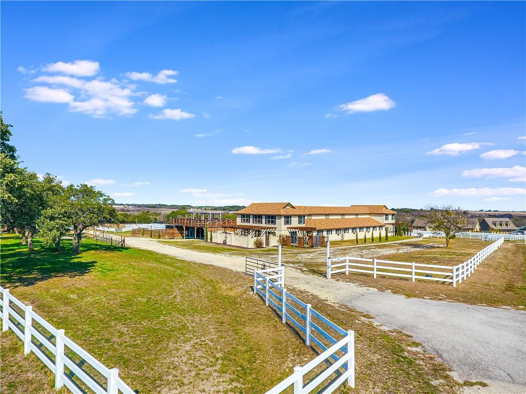 This one of a kind property is well designed for the easy care of your beloved horses. It is located in the gated equestrian community of Twin Creek Farms. Just 15 minutes to grocery stores, shopping, & hospitals. 45 minutes to Austin Bergstrom International Airport. Commercial horse boarding is allowed on this parcel. This property is 7200 sq.ft. which includes a 4440 sq.ft horse stable with 2760 sq.ft. of residential living quarters. The living quarters is split between the west wing and the east wing. The west wing is 2 stories, 1720 sq.ft., 3 bedrooms, one full & one 1/2 bath, living, dining, kitchen, & 2 private courtyards. The east wing is a 1040 sq.ft. studio/guest apartment on the 2nd floor with a full bath, kitchen, bedroom/living area, deck with awesome views, an office & 1/2 bath on main floor. Both wings have been beautifully remodeled to include stainless steel appliances, granite countertops in kitchen & baths, new windows, new HVAC in 2020, new vinyl plank flooring(west wing), & new paint. Two bedrooms & large walk-in closet were added to west wing in 2021. The stable includes 6 12X24, 4 12X12 stalls, plus 2 12X12 storage areas with water & electricity in each stall. It also has a hot water wash rack, hayracks, mat flooring, TV & DVD, & so much more. You can keep an eye on the horses in the stable through the window in the studio apartment or on your smart device via the cameras overhead. The property is fully fenced, gated, & cross fenced & includes a lighted arena, round pen, & several run-ins. 10 horses are allowed. A huge deck runs along the back of the building offering magnificent views of the entire property as well as long distance views of the picturesque countryside. This is truly the home where every horse wants to live.