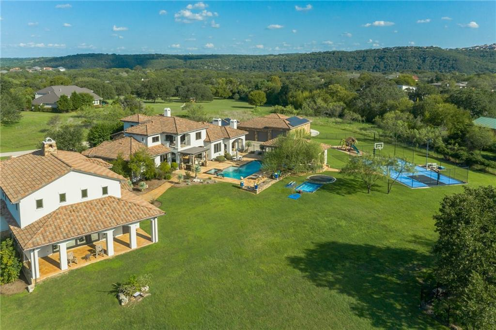 This one-of-a-kind estate on 4.75 private hill country acres is located in the gated, upscale community of Caslano. The front door opens up to a living area with views of the resort-style pool and cabana. Just past the wine cellar and dining room is the recently renovated kitchen that opens up to a gathering room. The owner's suite has also been renovated and features a spacious walk-in shower and stand-alone bathtub that makes you feel like you're at a world-class spa. Other first floor features include a lower level bedroom with a full bath, laundry room, and an arrival zone. The upper level opens up to a game room, three more bedrooms, and another full bathroom. Across the porte cochere is the separate guest suite entrance with a mini-kitchen and a full bath. The driveway opens up to a three-car garage. The two oversized sized doors allow you to park and pass-through with a boat or RV. Just behind the main garage is another garage with ample room for storage and additional parking for a car, golf cart, or ATV. Make your way to the north side of the property and open the door to the trophy room. This grand space features a one-of-a-kind fireplace, full bar, office, bathroom with a steam shower, workout room, and upper-level bedroom and bathroom. The lower level office has a secret panel in the bookcase that opens to reveal a cinderblock safe room with a one thousand pound safe door. Spend your time outside relaxing around the resort-style pool and cabana with a full kitchen, bathroom, pizza oven, and griddle. There's also a sport court with lighting and in-ground trampolines. Other property details include full solar panels, a well for the sprinkler system, landscape lighting, a sound system throughout the property, a fountain in the front circular drive with additional parking, security cameras inside and out with tv monitors/recorders that are located in the safe room. A once in a lifetime opportunity. Make it yours.