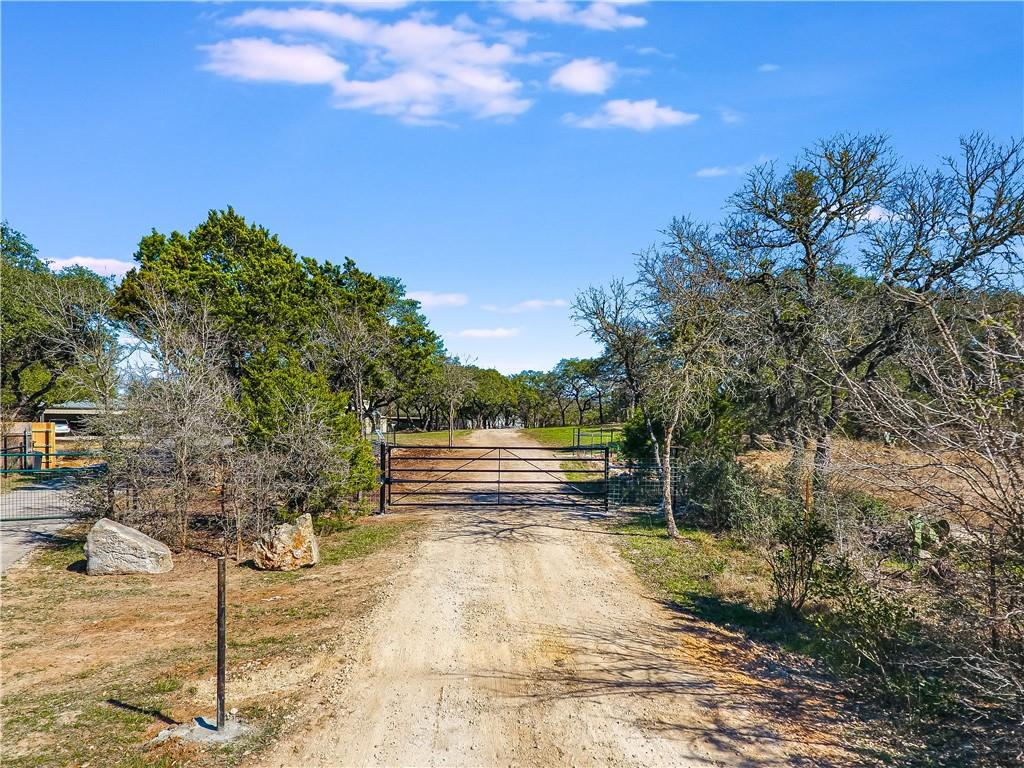 """Complete Package! This unrestricted Hill Country retreat offers a bit of everything. Multiple improvements, acreage & conveniently located 11 minutes West of I-35 & downtown San Marcos (no city tax). Features list above pertains to 1998 sqft house. Features list attached for 2 story, 3140 sqft, Guest/Barndominium. Check out virtual tour for more photos & aerial video! Additional features: 28x20 insulated garage/shop. 20x20 shop/storage. Multiple carports big enough for trailer, rv & boat parking. Multiple covered & uncovered patios, balconies & decks. Well house. 2 septic systems. 20x10 reinforced concrete """"safe room."""" Green house, garden area & fire pit. 10.5+- acres being combined & surveyed into 1 tract from 3. Land features: gated entry, circle drive, fenced & cross fenced, pen & shed, rolling terrain w/level areas, wet weather creek, bottom meadows, abundant trees, deer, migrating birds & other Hill Country wildlife. Secure & private. Easy going neighbors. House exterior freshly painted. Guest/Barndo has new siding."""