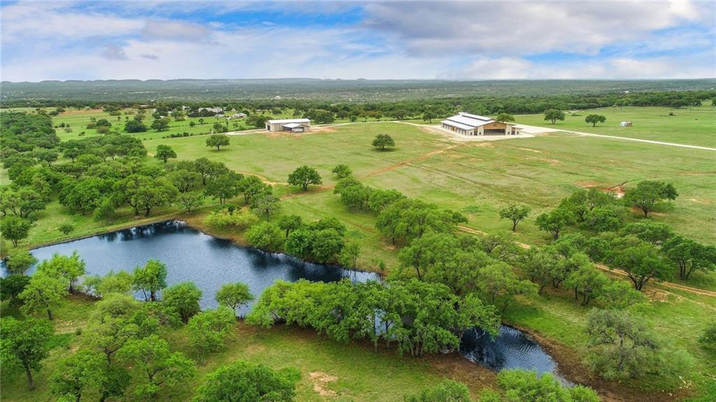 Elegantly designed 90.51 acre equestrian property minutes from downtown Johnson City, TX. The attention to detail and craftsmanship is unparalleled in this truly unique offering. This facility was built to perfection and includes 24 12x12 stalls that are all equipped with hay and grain feeders. There are 4 wash racks with hot and cold water, 2 on each side of the arena. The covered arena including stalls is 130x260 under roof.  The riding arena inside is 80x240. There are several tack rooms, feed rooms, an office, bathroom, and lounge. The arena is lighted with LED lighting. This property was designed as a dressage training/boarding facility and is the perfect place for even the most discerning equine professional. Also located on the property is a 50x130 hay barn that includes another attached covered area that is 50x75. Newly constructed roads have been installed for great access to and from the equestrian center.  Great water well and all underground utilities. The land is open with scattered mature live oaks, but does offer some wooded areas that have been parked out to perfection. There are 2 nice ponds on the property. This is truly a gem and is located in one of the fastest growing areas in the USA. Centrally located approx. 1 hour to Austin and San Antonio. Approximately 35 minutes to Fredericksburg or Marble Falls.