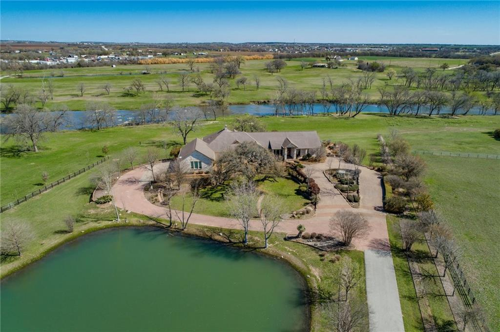 This spectacular San Gabriel River Waterfront Home resides on one of the most private communities in Georgetown. An incredible opportunity with over 400 feet of river frontage, an absolutely beautiful 5,600 single story home, a secluded and privately gated 14+ acres tract, filled with lush greenery, mature canopy trees, a half-acre pond loaded with Crappies, Bass and more.    ENTERTAIN IN STYLE Host parties in style with guests flowing between the formal living room and the large game room serviced with a full walk-in bar and the large outside deck.  The large kitchen opens to a hearth-warmed family room and is accented with a rustic beamed ceiling, richly grained granite countertops and warm wood cabinetry.  This welcoming home features dramatic and very large windows, providing a light-filled experience in almost every room, and allowing scenic views of both the River and half acre pond, at the same time.     The floorplan also includes 4 spacious bedrooms, 7 bathrooms, including 2 half baths, a cozy library, butler's pantry, formal dining room, living room, family/game room, laundry room, a 4-car garage and a kitchen Martha Stewart herself would envy.   Other notable interior features 6,250 sf clear span metal barn with 4 rollup doors, plenty of room for all your toys. An AG exempt property for lower taxes.