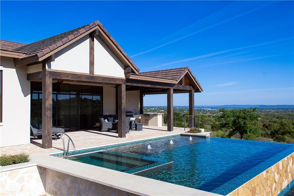 This beautiful well planned award winning custom home won People's Choice in the 2019 Hill Country Parade of Homes Tour, as well as the best living and dining area. It sits on a hill in the Overlook that is a subdivision located within the legendary Jack Nicklaus designed golf course at Summit Rock, a Horseshoe Bay Resort exclusive, members only preferred 18- hole course. With this location, one has a view of number ten and a view of Lake LBJ. The homeowner tastefully mixed opulent and Hill Country Modern elements throughout the home; from the gold plated crystal chandelier in the foyer to the custom wall of windows that lead to the vanishing edge pool and beyond. The home is surrounded on two sides with a greenbelt. The adjoining lot that protects the view of the lake is available. Owner is a Texas LREA.