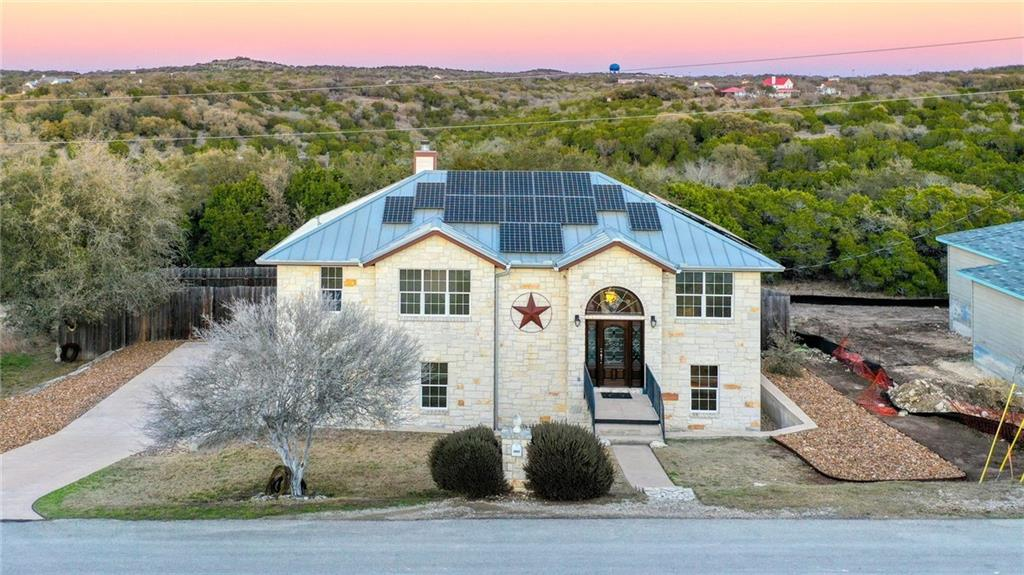The house that was created for entertaining! If you've ever wanted to be off the gird, this is a great home to get there: solar and rainwater irrigation system. Spend your time in this amazing home and enjoy so much of the hill country and the people you choose to spend time with. From the exterior kitchen and exterior bar, and inground swimming pool, the horseshoe pit, hammock, and a plethora of fruit trees and vegetables, it is a wonderland of outdoor Texas living.  Inside the home is an open concept on the mail level with the kitchen flowing into the main living room. A wall of windows overlooks the lush green hill country and a separate dining room with French doors has been converted to an office. There is a secondary bedroom, a full bath and on the main master suite on the main floor. Downstairs, there's a large game room and a full master suite downstairs. The large laundry room is located downstairs just off the garage and there is a huge storage area under the staircase. The outdoor balcony sweeps the entire span of the home. Lots of energy efficiency has been added to include solar screens, solar panels on the roof, and a water reclamation system. The swimming pool has extra sanitation with the smart pure ozone generator and Delta UV. It is the cleanest pool that you'll ever get in!  The 3 car garage boasts tons of built in storage, and stays cool with the spray foam insulation and insulated garage doors. The chimney was cleaned a few years ago in this home has been well loved and very well taken care of. Come and enjoy the best of living in Lago Vista!