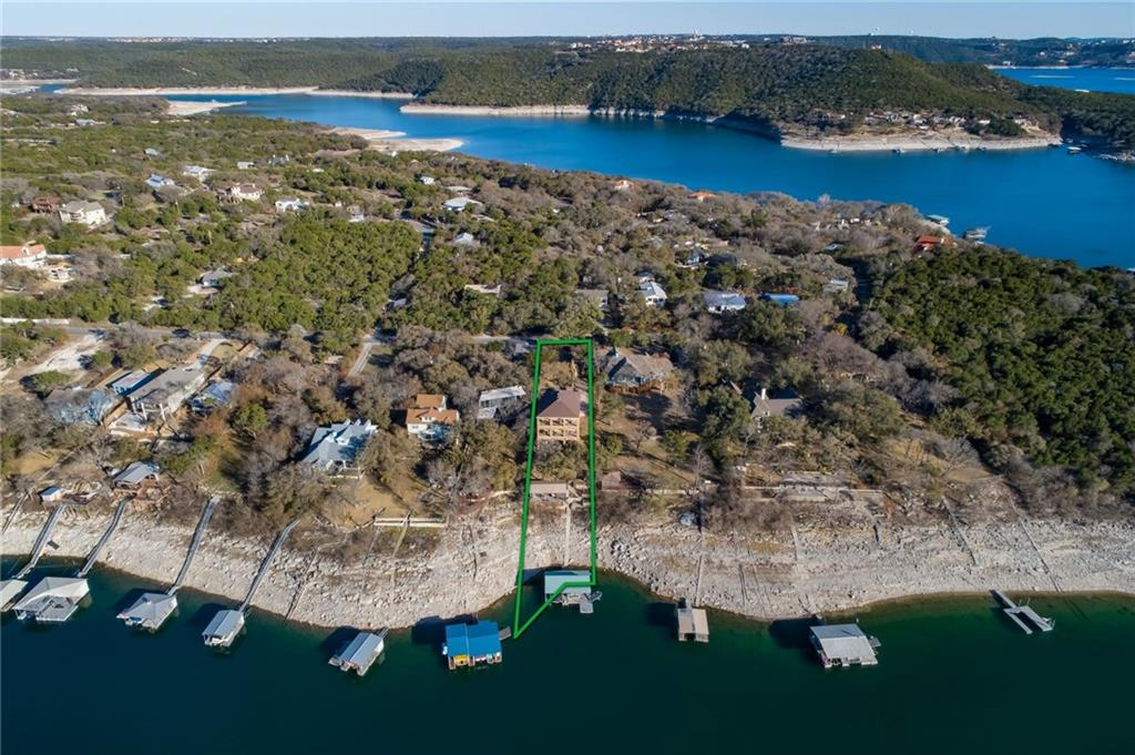 +/- 90' FEET OF WATERFRONT ON MACK'S CANYON COVE Over half an acre above Lake Travis with views that rival the famed Oasis Restaurant. The lushly landscaped property features a level back lawn that enjoys 90 +/- feet of waterfront with a large, covered boat dock plus a shaded party pavilion with plenty of room for lounging in the breeze after a spin around the lake. The elegant, three-story home is clad with native stone, columns of which frame the lake view from each of the terraces across the back of the structure.   THREE TERRACES EMBRACE THE VIEW The floorplan provides plenty of space to entertain, play and relax.  The top floor hosts the living, dining room and kitchen, providing spectacular views out over the water.  Glass doors open up to the covered terrace with an outdoor kitchen for alfresco dinners.  This level also includes a large theater with seating for up to nine and a wine room.  Bedrooms are contained on the main floor with both the spacious primary and second bedrooms opening out to the terrace and view.  A third bedroom and office complete the level.  PLENTY OF ROOM FOR FAMILY AND FRIENDS All three floors are accessed by an industrial elevator that terminates at the ground floor, a wide-open space with multiple uses; create a home gym, additional bedroom, playroom or man cave. This level opens to the lower terrace which features seating, dining and a hot tub. The pavilion, boat dock and lakeside are just steps away, perfect for accommodating friends and guests to spill out from the house and enjoy the water. The home is immaculately maintained and features quality finishes like travertine tile, granite and custom lighting.    24 Hour Advance Showing Notice.