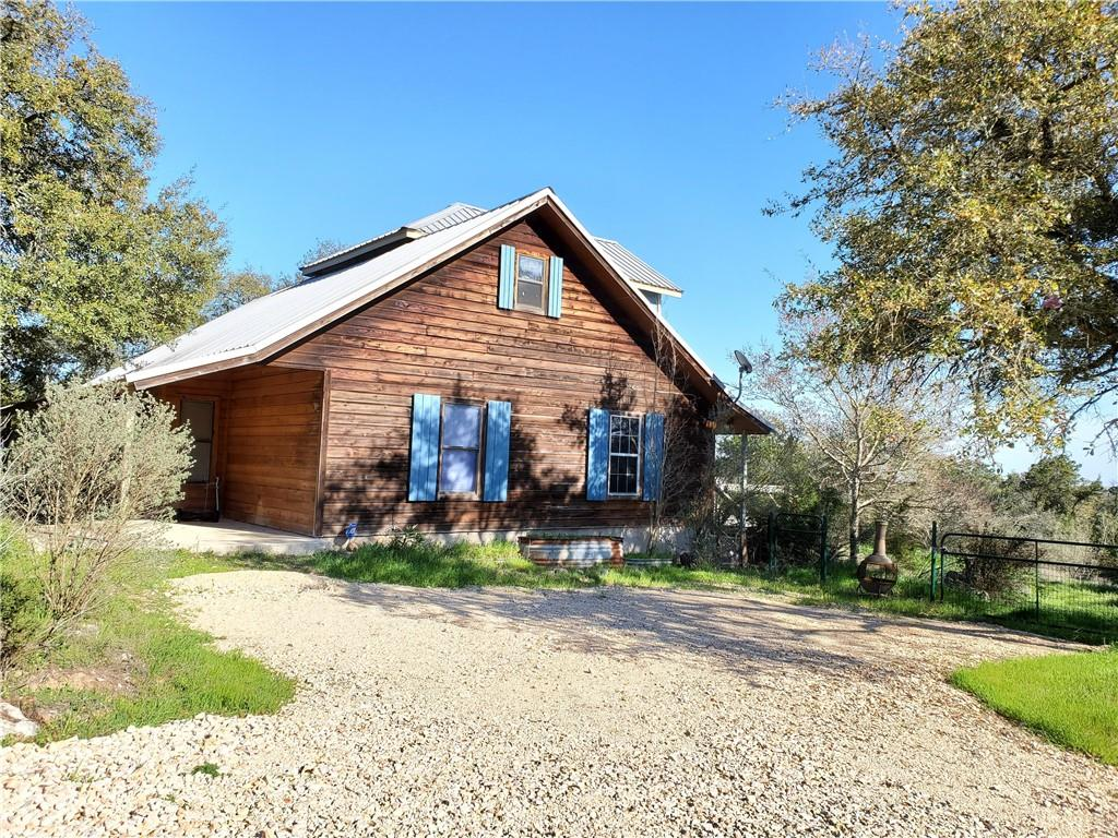 """OUTSTANDING million-dollar HILL COUNTRY VIEWS! 5.6+/- Acres of Hill Country Property boasts an abundance of mature oak trees and a wet-weather creek. Panel-wire fence w 6 gates, tool-shed-barn"""", PIRATE SHIP PlayScape, Zip-Line. Electric car charging station. Abundance of outdoor """"living-space""""-two natural fire pits, covered patio, wood deck & wood balcony with amazing views.  Inside -large open entry and foyer with beautiful interior finishes including tile throughout the first floor and new wall-to-wall carpet in all bedrooms and the second floor living room. MIL downstairs suites separated by kitchen dining room. Custom quartz countertops with waterfall edge in the kitchen complement custom cabinetry, commercial stainless fridge/freezer. Two bedrooms upstairs separated by vaulted ceiling living room with panoramic Hill Country Views. Recent updates with fresh paint, new doors, new LED lighting, new range, dishwasher, tankless water heater, low-flow toilets, and new tile showers."""