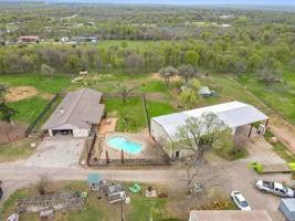 Single story ranch style home with pool and professional 3800 sq ft workshop, under roof equipment storage, fenced/cross fenced, 8 turnout pastures, round pen, 4 lean-to sheds, barn,