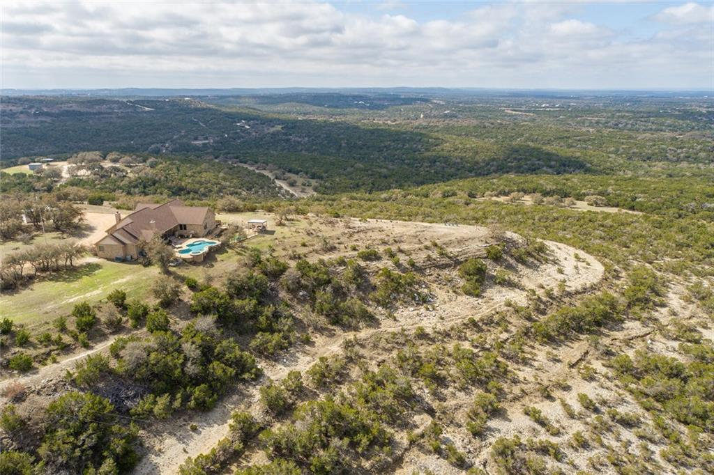 Never before offered 100 acre gentleman's ranch in Dripping Springs. Custom built ranch home atop one of the highest hills in the County. True panoramic views in all directions. This ranch has diverse topography, including seasonal creeks, waterfalls, and a swimming hole. The 5 bedroom, 3 bathroom home is perched at 1,340 feet overlooking the Pedernales Valley. With an open floor plan, the home is very comfortable, and makes living and entertaining easy. The Owner's Suite and dedicated office are at one end of the home, and the additional 4 bedrooms, laundry, and mud room are on the other. A deep covered rear porch provides outdoor living space in all weather: shade in the summer, protection from rain & wind, and a warm wood burning fireplace when it's chilly. The freeform pool and hot tub for year round enjoyment...swim under the moon, the stars. A two stall horse barn, round pen, chicken coop, tack shed, and storage shed are located between the main gate and the home. There are riding and ATV trails throughout the property. With wonderful topography, this ranch offers vistas, lowlands, and everything in between. This is a great hunting ranch, recreational ranch, or a great escape from the hustle and bustle of everyday life. With it's Wildlife Exemption, the yearly taxes are relatively low for a property this size. The excellent location to the NW of Dripping Springs provides easy access to the Bee Cave Galleria and Dripping Springs for shopping and dining, and is easily commutable to Austin. There are several local breweries, distilleries, and wineries in the area, and Reimers Ranch and Hamilton Pool Preserve are 10 minutes away, providing over 2,600 acres of Travis County parks to enjoy. Acclaimed Dripping Springs schools.This is truly a GEM of a property!