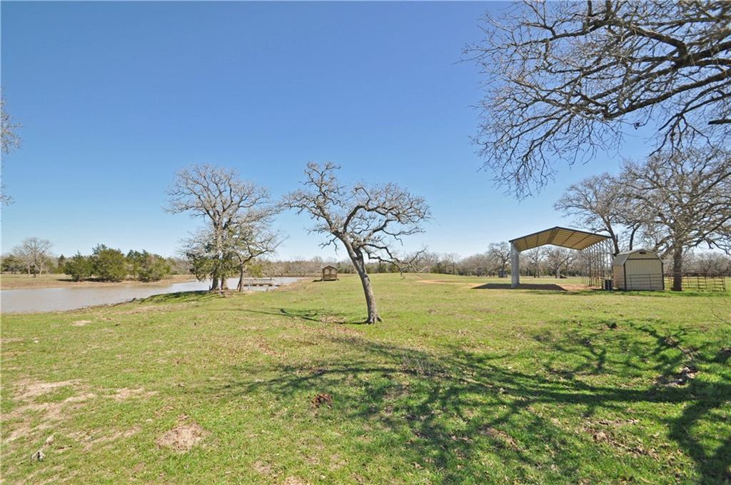 Approx. 20 acres to be surveyed out of larger tract. Beautiful 3-acre tank with dock. Perfect for building a home or enjoying as recreational property with covered RV spot including electric and septic. Open pasture sprinkled with oaks. Partially fenced (front and back property lines). Low taxes - ag exempt. Aqua Water Supply line at street - up to buyer to seek approval and reserve capacity. Can also dig well if preferred. Light restrictions to preserve property value: site built, barndominiums and newer mobile homes (2017+) welcome. Not in flood zone. 500+ feet of paved frontage. Conveniently located 10 minutes from downtown Smithville, 45 minutes from the Austin airport and 20 minutes from I-10, giving quick access to Houston and San Antonio. More land available in adjacent tracts at www.kovarcrossing.com.