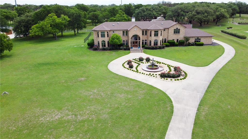 Gorgeous estate on 6 acres in Academy ISD. The first thing you will notice when entering the property is the extravagant driveway that leads to the entrance of the home and the 6 car garage on the side of the property. Grand entryway is a must see with the huge hanging chandelier as well as the curved staircase. Main living area overlooks the pool area and has a wood burning fireplace, recessed lighting, and stained concrete flooring. Dream kitchen is equipped with stainless steel appliances, double oven, granite countertops, large center island, updated ceiling fan, breakfast bar, and dining area. The master suite is outfitted with it's own private staircase, fireplace and incredible custom designed closet with your own private laundry. Outdoor amenities include a 20X50 in-ground pool set up for water polo, dog run and a 30X36 4 stall horse barn. The home also includes an attached 807 sq.ft. guest suite. Do not miss out on this great home, so schedule your private tour today!