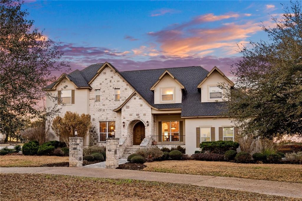 Spectacular Modern French Tutor Inspired Home with Hill Country flair!  Welcomed by a grand double wooden door, this limestone & stucco 4/3.5 home offers versatile living with an emphasis on the outdoors.  Beautiful wooden flooring throughout, downstairs boasts a dedicated home office, formal dining, island kitchen with granite countertops and sweeping VIEWS of the hill country. The 2-Story rock fireplace anchors the living area & the kitchen made for entertaining offers 5 burner gas stove with double ovens PLUS wall oven! Primary bedroom is HUGE with a bonus space for working out, yoga or library + a bathroom with double vanities, jetted tub, wrap around walk-in shower and 2 fabulous walk-in closets! Outdoors you will find a welcoming pool & hot tub with spillway & waterfall feature, flagstone patio with fireplace and built-in bar seating.  Second living space upstairs with 3 more bedrooms & 2 full baths. Backs up to Purgatory Creek Natural Area!!