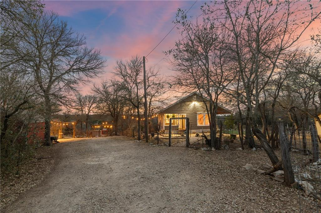 This hill country gem is absolutely stunning! Built-in 1929, the sellers transported the residence from 5800 Jim Hogg Ave (Brentwood) in 2013 to the top of their new 10.75 acre lot. Old warm charm flows throughout the house from the long leaf pine floorings to the shiplap ceilings. You can almost smell the delicious homemade meals that will be whipped up in the beautiful kitchen with updated, granite countertops. The owner's room is breathtaking with large windows, high ceiling and pine wood flooring. The primary bath has been completely remodeled and boasts a full tile surround in the shower, shiplap walls and a pedestal sink. The back of this home faces due West for unparalleled sunset enjoyment. The 12x20 detached guest suite is incredibly charming and is perfect for overnight guests, a studio or office space. This home was made for entertaining with a fantastic bar area, fire pit area, and multiple porches. Lush hill country views can be seen for miles. Definite further potential for gardening and raising livestock.  Spray foam insulation added in 2014 + metal roof, electrical, plumbing and HVAC.  2800 gallon water reservoir and a deep well that provides the most delicious water. Only 45 mins to DT and only a few short minutes to the Blanco River. New septic to be installed.  Bubbling spring at bottom of property!