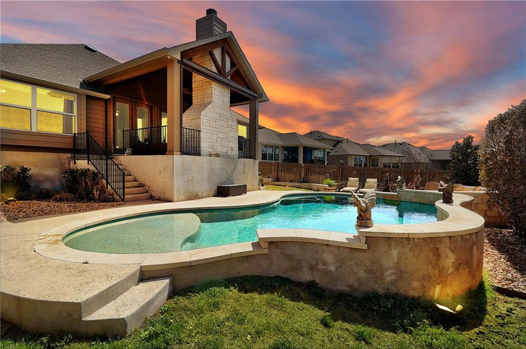 You have a paradise staycation every day in this gorgeous home with a resort-style pool and covered patio with a stone fireplace. This home screams luxury and meets the approval of those accustomed to the best quality design, finishes, and lifestyle. Impressive wood-look tile floors seamlessly take you from room to room. No money was spared with the updates that include surround-sound system w/ volume control throughout the home, custom landscape and motorized exterior shades, huge custom built-in closet, and coated garage floors, to name a few. Entertainers' and chef's dream with its open and sunshine-filled layout, multiple dining areas, and a beautiful kitchen, with a large center island and SS appliances, adjacent to a sizable breakfast nook. The primary suite calls for relaxation with its glamorous en-suite bath. MIL floorplan and spacious rooms add privacy and will make your guest feel right at home. You will love staying and coming home!