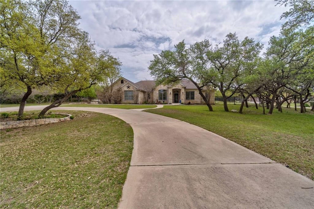 TALK ABOUT GREAT LOCATION!!!!  This one story home on 1 acre is located in Hidden Springs, within walking distance to the high school, and 5 min to downtown Dripping Springs. From the street you are greeted by a circular drive and landscaped front yard, enter the bright and inviting home and your eyes are instantly drawn to the wood floors and crown molding in the living room & dining room, floor to ceiling stone fireplace and large windows to the backyard. The kitchen has tons of cabinetry, granite counters, stainless appliances and a center island and it's open to the living room and breakfast room. The master suite features tray ceilings with crown molding, direct access to the back patio, large bath with double vanities, soaking tub and separate shower, and walk in closet. The house is 2587 sf, 4/2.5, plus 1000+ sf air conditioned shop with one bath, which can be used as a pool house, game room or guest house. The backyard has plenty of room for a pool and is completely fenced, with a covered patio with tongue and groove ceiling and ceiling fan.  This hill country home is ready for you to make family memories!