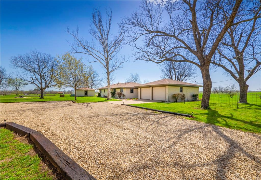 This property has 12.95 acres with breathtaking Texas sunrises and sunsets at this secluded, yet convenient homestead! The open living room, kitchen and breakfast/dining area offer great space for get-togethers and in the evenings a star filled sky can be enjoyed by the fire-pit. Country kitchen has a lot of custom cabinet storage as does the breakfast room and the three hallway closets. Wood flooring which is not only beautiful but easy to maintain! Nice breezeway between house and garage and a large covered back porch. Very versatile outbuilding that has plumbing, electrical (two 220-amp outlets one for cooking another for processing equipment), gas available (hot water) and window unit. This building also has a large walk-in cooler (with aging hooks) – great for processing deer, beef, hogs, or chickens. Could also serve as an office or an apartment separate from the house. The front 10 acres is cross fenced with offering 16 separate paddocks, with well-established coastal bermuda grass, 3 access gates, and perimeter and interior electric fencing with the charger supplying 7300 volts. Approximately 60 pecan trees that allow for ag exemption, eight peach trees, 6 plum trees, asparagus, and artichoke plants, large 2000 square foot garden with drip irrigation to each plant. The four-bay concrete tractor shed is 20' x 60' with an additional 18' x 20' covered area attached.
