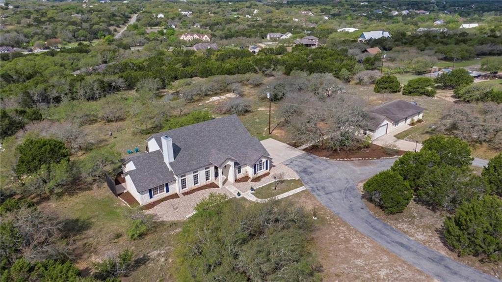 5+ acres located in AUSTIN, TX and The HILL COUNTRY also located in the exemplary Dripping Springs ISD! You can have it all with this property offering a beautifully updated main home, a one-story detached guest home, fully fenced acreage, your own pond, high fenced garden area, small covered barn waiting for your donkeys, horses, or goats, fire-pit, and sunset hill country views off the back porch or balcony. The main home is approximately 2,676 sqft and has 4 bedrooms and 3.5 bathrooms; the primary bedroom and guest room with a full on-suite bathroom is located on the main level and upstairs have two oversized bedrooms with a shared jack-n-jill bathroom.  The guest home is approximately 1,032 sqft with a large living area, office/study/den, a primary bedroom with a walk-in closet, and its own garage. There is well water with a 2,500 gallon storage tank and rainwater collection as well.  The roof on the main home was just replaced in late 2020!  Austin living, Hill Country views, Dripping Springs Schools, Land to call YOUR home, THIS IS IT!