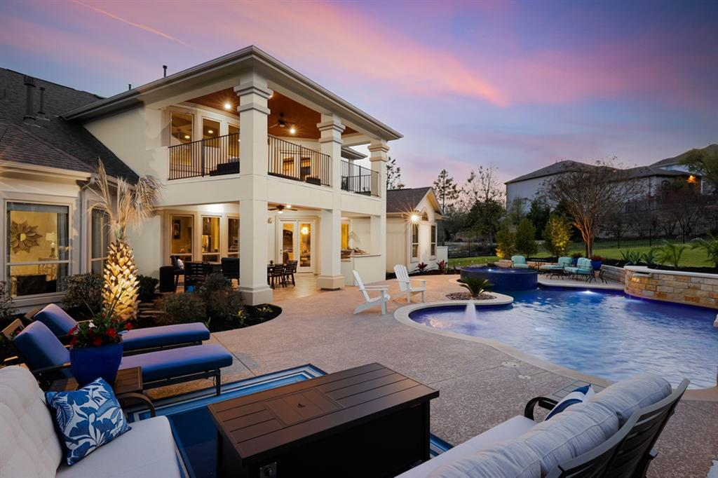 A hill country oasis, this former model home is complete with every upgrade, along with a luxury resort-style pool. Upon entering the double steel doors, the 20' ceiling foyer guides you into an open-concept living area, abundant with natural light from expansive windows. Enjoy the picturesque view of the lavish pool and spa, while listening to the custom water features. Ideal for entertaining, the home features a fully covered exterior kitchen with dining area, and a spacious yard sitting on half an acre. Both the primary suite and full guest suite are located on the main level.  The additional three bedrooms are upstairs, accessible via the dual staircases. Relax with a movie in the home theater, or entertain in the game room with connecting second level covered patio, overlooking the scenic yard below. 4 car garage allows for multiple cars and abundant storage. Furniture is for sale separately. Enjoy the Travisso lifestyle, complete with community clubhouse, gym, pools, tennis courts, and miles of hike & bike trails.