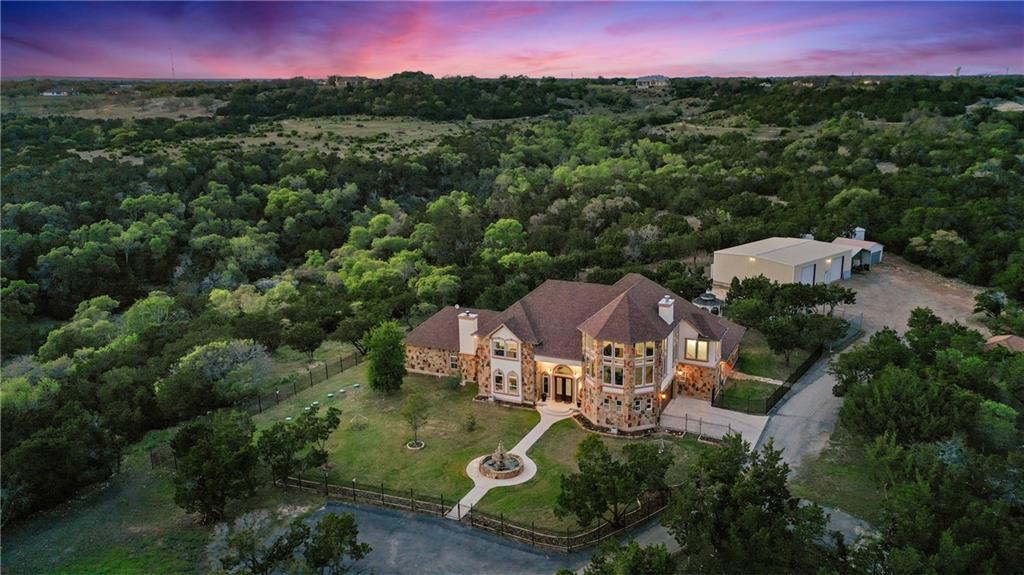 **Multiple Build-Sites on Property** Perfectly poised on a hilltop, with expansive, 360-degree views of rolling green, sits a luxurious estate with the utmost in privacy and comfortable living in the Texas Hill Country. Fifteen wooded acres of mostly Oak, Walnut, and Cherry trees envelop this custom-built, five-bedroom home with a large workshop. Custom cabinetry, custom windows, rare wood floors imported from Germany, and so many more items of quality pervade throughout the home. The primary bedroom, on the main level, is impressive, with soaring ceilings, a private covered porch, a fireplace, and an ensuite bathroom with all of the bells and whistles. The kitchen is a masterpiece, large enough for twenty people, and loaded with top-of-the-line appliances. This is an exclusive, family compound that sits just twenty minutes away from The Domain and forty minutes from Downtown Austin. Quality and elegance melded perfectly with Hill-Country charm, this beautiful estate is the perfect combination of taste and comfort!