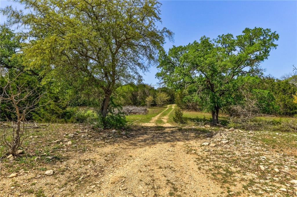 Do not miss out on this gorgeous 30.64 acres in Liberty Hill on which to build your dream home....a rare gem! This property is fully fenced, and ready for you to bring your animals (large and small) to make it a home. Through the pipe entrance, you will find a wet weather creek with culvert to cross over into the property. The heavy tree cover around the creek makes the property extremely private, so build your home where you wish and know that privacy is there! Behind the trees you'll find a spring fed stocked pond....perch are just waiting to be caught and adventures to be had! This also serves as a great water source for your animals. There are several clearings on the property nestled between the groves of tress that would be perfect for a homesite, barn, or workshop. Being cross fenced, it would be easy to bring your equine friends and let them have several acres to roam and graze. Located about about 15 minutes from downtown Liberty Hill, less than 30 minutes from all that Leander has to offer, and less than an hour from Austin. Work in the city, live in the peace and quiet of the country!