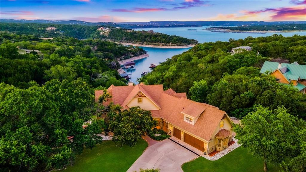 Magnificent Sunrise Cove estate, in the waterfront community of Lakeshore Ranch. Situated on approximately 3 acres, this gated property is tucked away at the end of a quiet cove. A lush spring-fed creek flows through the middle of the property, into Lake Travis. Enjoy interior panoramic views from your expansive veranda overlooking your private backyard oasis. This custom estate was designed for entertaining and indoor/outdoor living, with two large patios, one includes a custom fountain with cedar swings and the other includes a large firepit, handmade smoker & a pond. Warm and inviting finishes throughout including vaulted ceilings, fireplace in the family room & Alderwood cabinetry in the open kitchen. The oversized center island, equipped with a built-in wine fridge, opens up to the breakfast area overlooking Lake Travis. On the main level, you'll find a dedicated office with dual glass-paned french doors, and a secondary bedroom that can double as another office. The primary bedroom is on the main level and features a vaulted ceiling, doors that open to the covered veranda with lake views, a very spacious walk-in closet with built-ins, and a large bathroom equipped with double vanities and a walk-in shower with dual showerheads. Both downstairs secondary bedrooms have en-suite bathrooms that open into a center family room. 3 living areas include a formal living, family room, and an upstairs flex /media room with a wet bar and ensuite bath, which could alternatively be used as additional living quarters. 3 car garage, a separate RV / Boat garage, with potential for additional living quarters, and a circular driveway. Lakeshore Ranch offers a private boat ramp. Exemplary Lake Travis ISD. Tax Rate 1.88 & voluntary HOA is $50 per lot, per year.