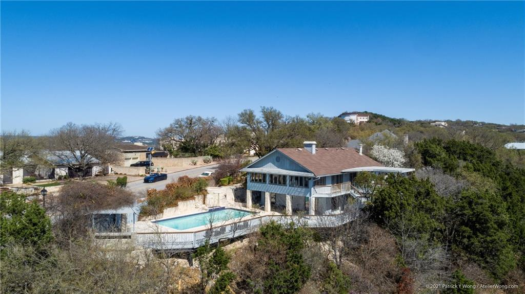 Located on one of the most recognized and prestigious streets in Austin, this home has the very rare view of both Lake Austin and the unobstructed, entire downtown skyline.  Mt. Bonnell is the highest point in the city.  From either level of the decks or the great room, the sun and moonrise over the skyline has to be seen in person.  With an open floor plan on the main level, large kitchen, spacious decks and pool, it is made for entertaining and making memories with your family and friends.  The main bedroom has a fireplace as does the great room.  On the pool deck level are three bedrooms each with its own full bath.  These or other rooms downstairs are ideal for offices.  The kitchenette / wet bar is easily accessible from the pool and large pool deck.