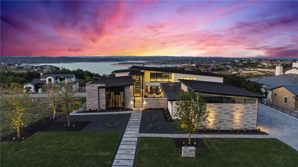 Immaculate modern luxury home custom built by Laurel Haven Homes in the prestigious gated Peninsula at Rough Hollow.  Situated on a large elevated lot to enjoy spectacular views of Lake Travis throughout. Enter the home through a private courtyard to find a stunning masterpiece constructed with the highest quality materials and meticulous attention to detail.   A true indoor outdoor flow with walls of glass that look over the expansive outdoor entertaining areas and sparkling pool to breathtaking lake views beyond.  Huge scale with 22' ceilings in the open main areas boasting fantastic natural light. A Smart home, with Crestron controlled media, lights, shades, climate, doorbell and security cameras. Well thought out floor plan of 6,059 square feet all on one level  including four bedrooms each with large ensuite bath and closet, an executive office and a media / game room made for entertaining and relaxing.  Gourmet, modern Chef's Kitchen features Gaggenau appliances, elegant Quartz counters and River City custom cabinets.  The private sanctuary of the Owner's suite enjoys incredible lake and pool views and boasts a spa-like master bathroom unmatched in glamour and design. Stone and innovative Western window systems grace the exterior for a sleek, state of the art style. Four car garage with commercial grade garage door openers, epoxy floors and electric car charging station.  The backyard is an outdoor oasis with expansive stone patios, al fresco dining area, top of the line outdoor Kitchen with grilling and smoker stations all overlooking the enormous pool and spa with luxe dark pebble sheen finish and incredible lake views. Enjoy the lake lifestyle with the resort style amenities of Rough Hollow - private marina, gourmet restaurant, fitness center, miles of hiking and biking trails, tennis, parks and more. Located within the highly ranked Lake Travis school district moments from the conveniences of Lakeway, this unique and special offering has it all.