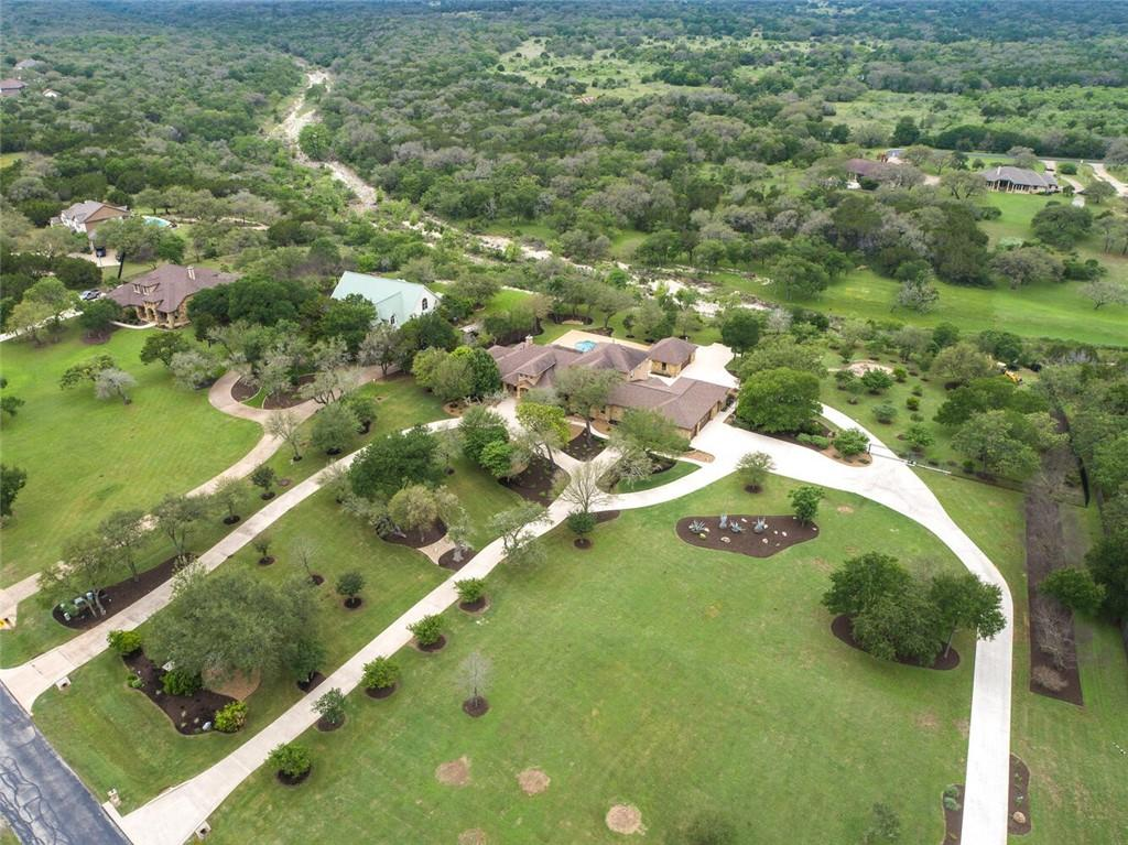 """This stunning estate is located in the prestigious Bluffs at Onion Creek, in Ruby Ranch.  With gorgeous sunset views out over the Texas Hill Country, the home sits above the banks of Onion Creek.  Enjoy the scenery while sipping your favorite beverage and lounging around your pool.  The hot tub is the perfect spot for viewing the starry skies and relaxing after a long day.  The home offers 6 bedrooms, 5 1/2 bathrooms, a dedicated office, two family rooms, a large laundry room, two walk-in pantries, front and back porches, an upstairs balcony, pool and spa, pool house/garage with an outdoor shower, irrigated raised gardens, fruit trees, fire pit and telescope stand on a stone patio, wrought iron fencing, and amazing Hill Country views.  As a bonus, the owners added space to the home which was used as home offices and schooling areas.  It was designed to be easily transformed into a full guest house, all under one roof.  Building plans are available!  The """"safe"""" room, located in the garage, is climate controlled and has internet connection.  There are security cameras on the interior and exterior of the home. The 45,000 gallon underground water storage tank captures rain water, which is used for all of the automatic sprinklers throughout the property.  There's an RV hookup around the back of the pool house and a place to park it out of site, in order to comply with the Ruby Ranch HOA.  Great schools, close to shopping, dining, wineries, distilleries and breweries. This property has a little something for everyone...and so much more.  Don't miss the Matterport tour!"""