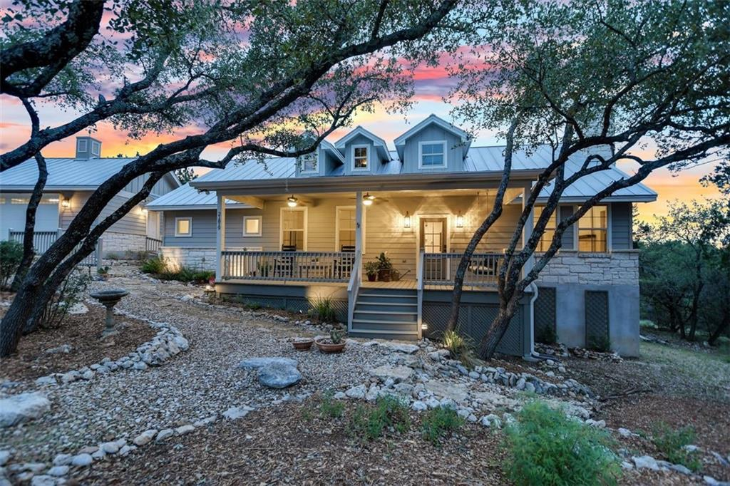 Ease into your own corner of heaven in this secluded modern farmhouse nestled in the Lago Vista woods & overlooking the Texas Hill Country! This home delivers comfort, character & charm like no other. The extra-large & extra-private lot is surrounded by woods – at the top of a hill—and at the end of a quiet cul-de-sac. Plus, there is plenty of room for adding a casita, pool or greenhouse. The delightful, open-concept Living/Dining/Kitchen is spacious & homey w/ an abundance of natural light, rich hickory floors, a graceful floor-to-ceiling tapered fireplace, extra-wide country style window sills, & dramatic ceilings. The gourmet Kitchen includes high-end stainless-steel appliances, 2 ovens, a porcelain farmhouse apron sink, impressive granite countertops, intricate cabinetry, & a spacious pantry. The main-level Master Suite is beautifully sunlit & roomy w/ private access to the country back porch. The spacious Master Bath features Brazilian granite, luxuriant garden tub, large stand-alone shower, & walk-in closet with custom shelving. A large, main-level Guest Ensuite features a 10-foot ceiling & its own bath. Upstairs, a large 3rd Bedroom/Office has exceptional privacy w/ its own Full Bath & sole access to a tree-top deck w/ jaw-dropping views of the Hill Country. The detached garage is oversized & has ample room for storage w/ a tall door to accommodate pick-ups & SUVs. This nearly one-acre, heavily treed lot is unusually private, tranquil, & scenic. It's like your own private nature-preserve with Texas white-tailed deer, countless varieties of songbirds, & other wildlife on hand. These stunning porches & decks are perfect for sipping morning coffee, enjoying colorful beverages at sunset, & gazing at the Great Milky Way on starlit nights. This home is just 5 min from Lake Travis & near the magnificent Balcones Canyonland National Wildlife Refuge & beautiful Bar K Park with pavilions, athletic fields & other amenities.