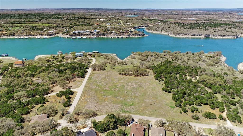 Rare opportunity to own 16 acres of residential or multi-family waterfront acreage in Lago Vista. This rare piece of land offers many opportunities for Multi-Family, Residential, or Mixed Use (wedding venue, marina, etc.). You could put several condos, homes or duplexes on it, have a large waterfront estate, build waterfront estate homes on it, or develop a business venture with waterfront access and rights. Plat available from when it was originally planned to be developed. Survey also available. Panoramic views with water rights to put docks, all with deep water access. Land is level with easy build areas. Electricity runs across site and water and sewer lines are at the front of the lot on Patriot. Property is part of the Lago Vista HOA which allows access to all waterfront parks in Lago, fitness room, pools, playgrounds and more! Buyer to verify all build requirements, utilities, and restrictions. Information is deemed reliable but not guaranteed.