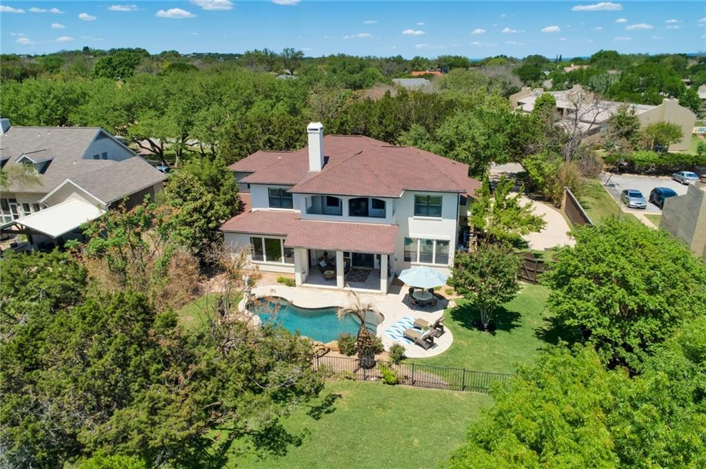 Lakeway custom overlooking 12th green and fairway at Live Oak. Covered patio space overlooks waterfall pool, golf course, and mature landscaping. Custom built by Laurel Haven. Excellent kitchen is open to living and features; stainless appliances, granite surfaces, double oven, and stone travertine flooring. Soaring ceiling in the formal dining, open and bright with lots of windows. Large master bedroom with separate closets and sitting area. Office is on the main level with beautiful hardwoods and built in book case that opens into secure storage area. Covered view patio off game room with commanding views of 12th green and Hill Country.  Circle drive leads guests into tree covered front yard area where they are greeted by custom iron and glass front door.  This is the floorplan that everyone is looking for; 4 bedrooms, 2 living, and office on main level.  LOW tax rate and NO HOA which means NO fees, and more money in your pocket!