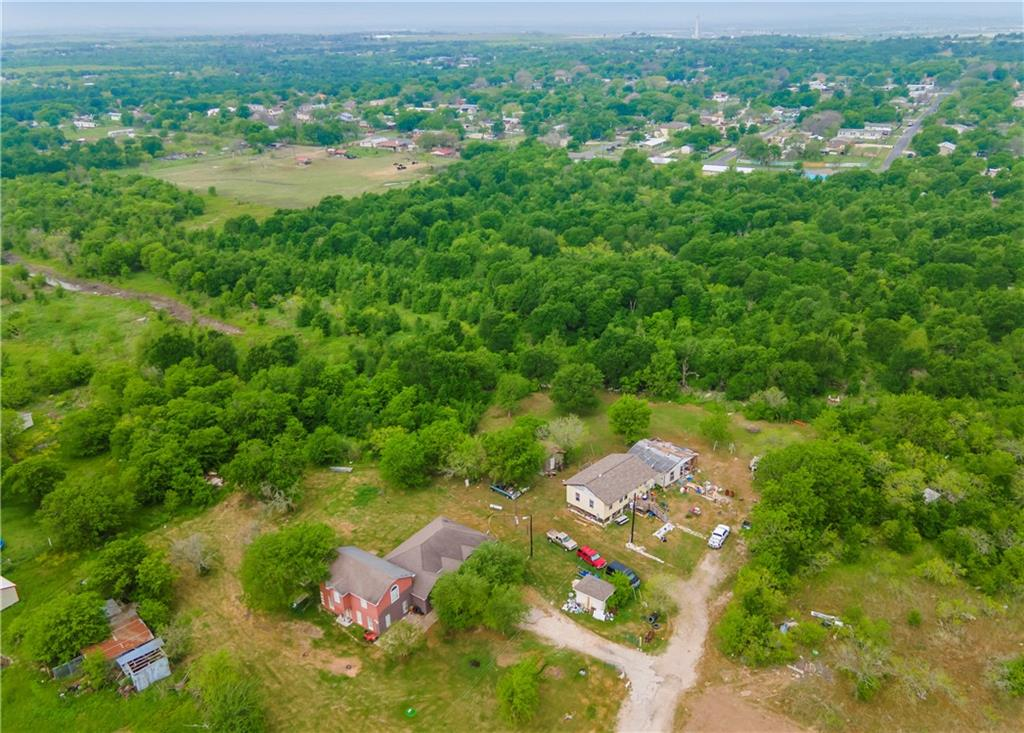 Spacious floorplan on 13.31 acres with tons of potential! Minutes from COTA. Four bedroom, 2.5 baths with bonus room. Large kitchen with granite counters and plenty of storage and workspace. Tile flooring, coffered ceilings. Large bonus plus a flex room that could be used as an office.