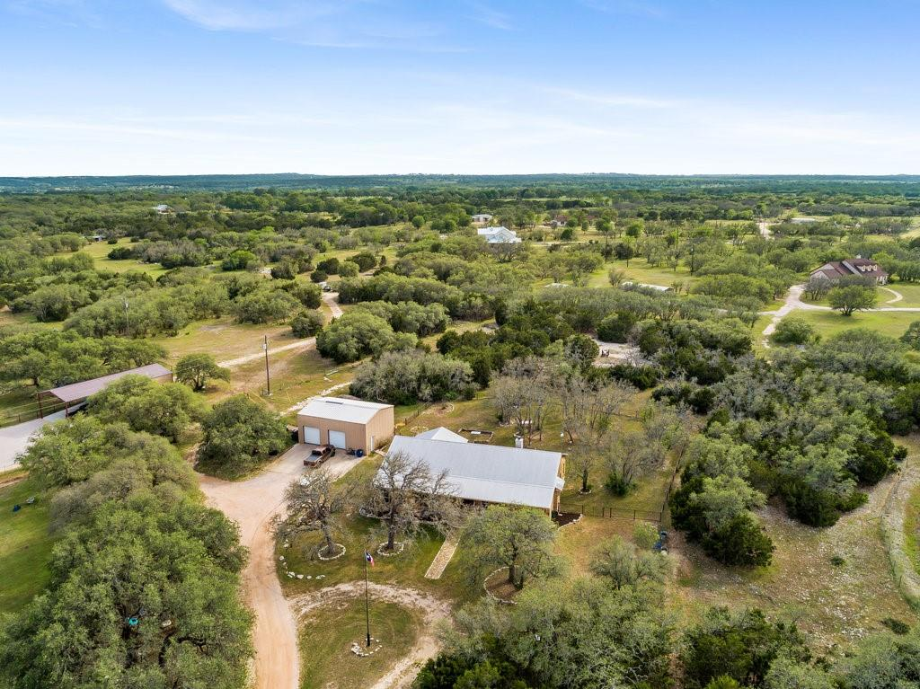 Beautiful 10 acres sprawling with mature trees in the most desirable area outside of Austin in Liberty Hill with wildlife exemption for minimal taxes. The workshop boast 1200 sq. ft. for any man's dream work area or can be used for 3 car garage. Not included in the sq ft of the workshop an unfinished bedroom and bathroom. This custom built home in 2008 spared no details. Beautiful front and back porches to enjoy the sunrises and sunsets. As you enter the property, the custom electric iron gate boast address of the property. The property is fenced around the perimeter of the property and has use for wildlife exemption. The home has room for everyone, with large bedrooms and two master suites that is great for a mother-in-law. Storage everywhere. Beautiful custom alder wood stained cabinetry throughout the home. Cathedral ceilings with large beamed ceilings shows the size of this large area. Owner has taken price and attention to detail throughout the home. The kitchen, dining, living having open concept makes it a great place to host family gatherings. This won't last long.