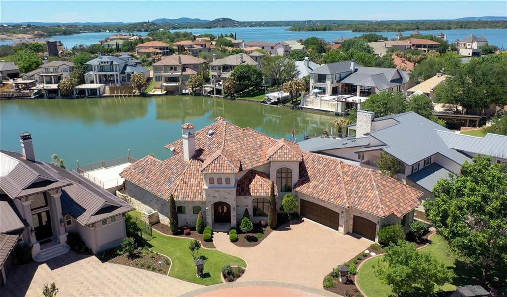Beautiful custom home on Lake LBJ built by Cave Johnson in the luxury gated community of Applehead Island. The open floor plan provides ample space to entertain large groups. The MAIN LEVEL features a beautiful entry with views of the lake, hills and infinity edge swimming pool. Plenty of space to relax or mingle in the Great Room or Retreat--both have lake views and gas log fireplaces. The Great Room has travertine tile flooring and the Retreat has rich hand scraped Ash wood flooring. The master suite is on the main level with lake views and pool access. The open kitchen features granite counter tops, breakfast bar, island, gas cooktop, pot filler, double ovens, warming drawer, walk-in pantry and butler's pantry. There are two dining areas. UPSTAIRS is a third living area with coffee bar, beverage refrigerator, microwave and built-in Murphy bed (for 4th sleeping area), plus two bedrooms each with balconies with lake views and ensuite bathrooms. Quality materials and finishes are throughout the house with solid wood doors, crown molding and more. The boat house features 2 boat slips: one has a hydraulic lift and the other has an electric lift. The 3-car garage can be used for 2 cars plus a heated/cooled workshop in the third bay, if desired. This well designed home is a treasure. The Applehead Island POA has a recreation center with tennis courts, community pool and party area. Homeowners may receive a Club Initiation fee waiver to Horseshoe Bay Resort upon acceptance by The Club.