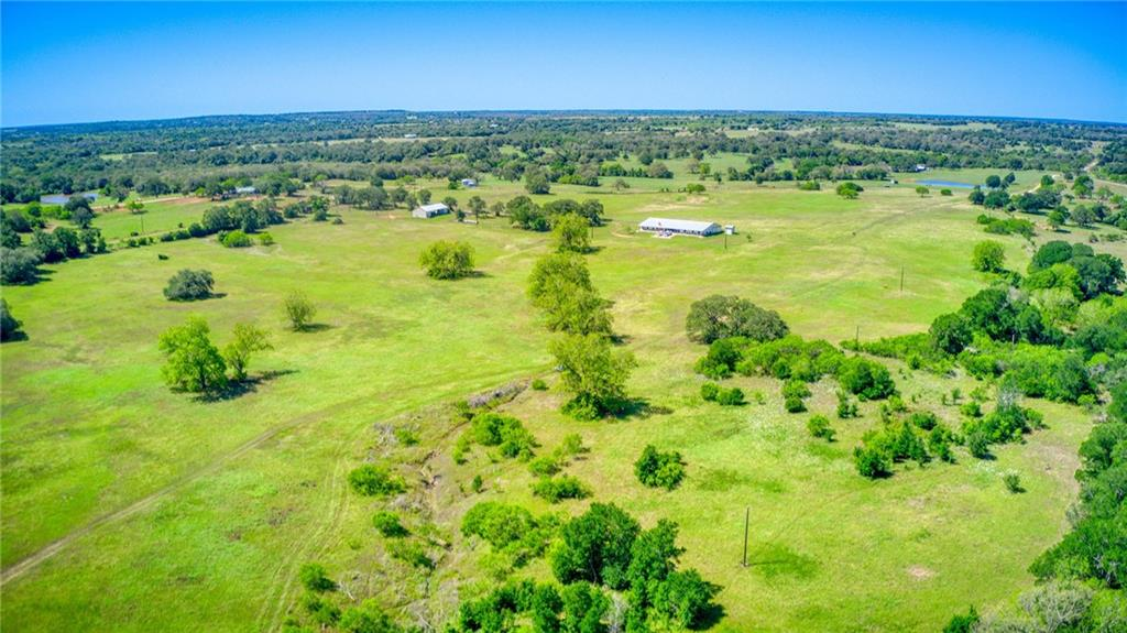 THE most spectacular recreational ranch on the market is in Gonzales, Texas! 117+ acres in an amazing, private location, just minutes from the Palmetto State Park and just happens to have more than one mile of river frontage on the San Marcos River. Hunters will appreciate the abundant wildlife. Equestrians will enjoy the seven spacious stalls, large pipe fenced paddock and first class horse facilities. Anglers can fish till their hearts content on the San Marcos River, which also includes all the water activities such as kayaking.  Livestock will thrive on the thick, lush improved and native grasses. You can even harvest pecans from your own 28+/- ac  river bottom covered with large native pecan trees! After a long day of playing, relax in your own, fully equipped, luxury 2/2 main home while guest stay just across the breezeway in the guest quarters, that has it's own kitchen, laundry, bath and oversized game/flex room. The finishes in the main home and guest quarters are second to none! Just so happens both come furnished! Apartment, guest quarters and horse barn is all under one metal roof. General layout is comparable to a barndominium style build. Construction is low maintenance galvanized metal framing and insulated panels. Covered front porches in front of apartment & guest quarters. Oversized covered porch area/ breezeway between main home & guest quarters. An equipment barn also has an office and well house includes a filtration system and storage tank. A 235 gpm artesian well provides all the water to the property. All minerals owned by seller shall convey to buyer, believed to possibly be 25%. This property is unrestricted and wildlife exempt. This is the perfect end user ranch home or possible corporate retreat/event center that can easily entertain large groups of people with unlimited outdoor activities.