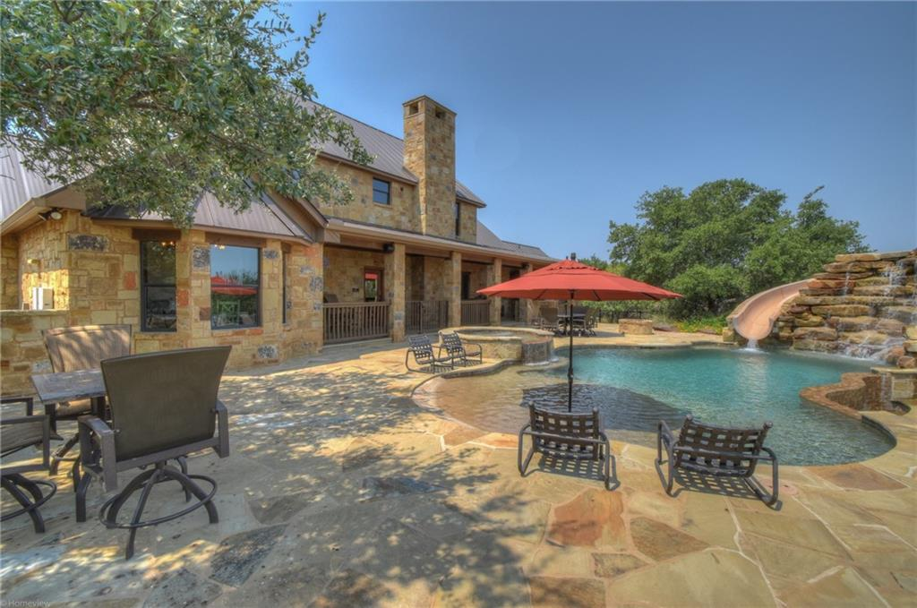 Luxury hill country home in Horseshoe Bay on almost 11 acres with spectacular views of Lake LBJ. The home was remodeled in 2015 with quality materials and finishes throughout. The home has an open floor plan and each of the 6 bedrooms has an ensuite bathroom (primary bedroom and bedroom/office on main level). The gourmet kitchen has a view of Lake LBJ from the kitchen sink, a large island with breakfast bar, beautiful granite counter tops, basket weave tile backsplash, stainless steel appliances, gas cooktop, wall-mounted pot filler faucet, double ovens, microwave oven, ice machine, refrigerator, knotty alder custom cabinets and walk-in pantry. There is a gas log fireplace in the great room and the home has a complete audio system with six zones. Flooring in the common areas is wood plank tile, stairs are hand-fired tiles from Italy and bedrooms are carpeted. The primary bathroom and closet is exquisite with separate vanities, a spacious walk-through shower, a soaker tub and a huge walk-in closet. The backyard features an outdoor kitchen with gas grill and wet bar, gas fire pit, fabulous swimming pool with infinity edge spa, a pool slide and a towering rock waterfall, an outside shower and poolside bathroom. The property is completely fenced with walking trails and offers an occasional stream running through the property. Vast parking and storage is on-site: 2-car ATTACHED garage, an oversized 2-car DETACHED garage (or barn or workshop) and two carports for boats or an RV. Horses are welcome in The Hills subdivision. The property is ag exempt.