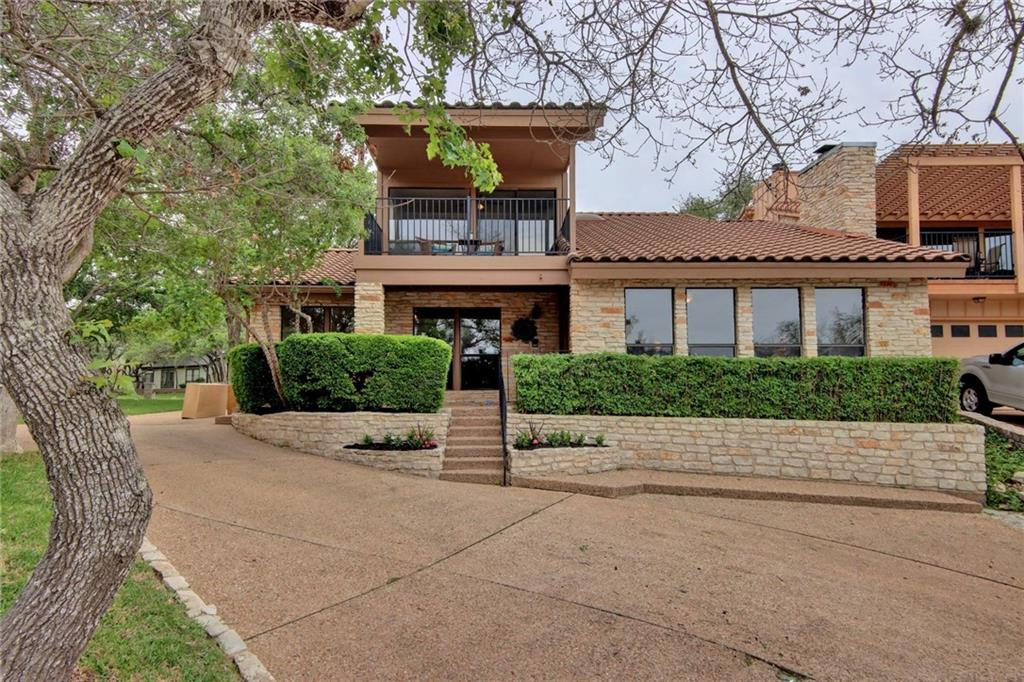 This tastefully remodeled home in sought after Lakeway is a must see! Enjoy resort-style living in this gorgeous home with soaring, beamed ceilings, rich wood flooring and a flawless, open concept floor plan. The visually dramatic living space boasts custom built-ins on each side of a floor to ceiling, rock fireplace. A large wall of windows drenches the room with natural light and connects the home with the outside space (new windows will be installed in 2 weeks). Play bartender at the large wet bar with a sink, built-in refrigerator, open shelving and tile backsplash. The gorgeous, remodeled kitchen features white cabinetry with a custom tile backsplash that spans from the quartz countertops to the ceiling. The open-plan design allows the cook to chop, stir and socialize all at once. The expansive, main floor owner's room is wrapped in windows, allowing natural light to pour inside. Prepare for your day in the gorgeous, recently remodeled ensuite bath with a spacious dual vanity and shiplap walls. 2 large guest bedrooms reside on the 2nd floor, one of which with direct access to the private balcony. Zoned for highly rated LTISD and only a few short minutes away from Lake Travis. If it's a low-maintenance lifestyle in a premier location you're after, this home is hard to beat!