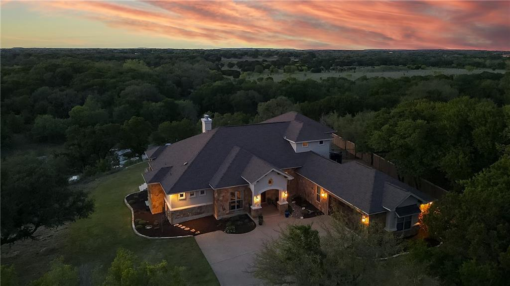 Riverfront sunsets and sunrises are equally breathtaking at this custom home perfectly situated on over 2 acres overlooking the San Gabriel River with huge live oaks scattering the property.  Centrally located with space, privacy, views from every room, this home defines country living with modern convenience.  Built in 2015, every detail was considered during the design. Too many features to list, but include handscraped wood flooring throughout the main level with tile in wet areas, high beamed ceilings, stone accent walls, gorgeous lighting and plumbing fixtures througout, and a primary suite you have to see to believe. The layout provides the functionality of main level living with 3 bedrooms, 3 baths, a private office, a second story for flex space…and priceless views. Gourmet kitchen with huge center island, walk-in pantry, and open to the large dining and living areas. Fenced side yard, large utility room on the main level, and a large garage with extra space for a workshop or place to park your UTV or golf cart. Walk down to the river, or just enjoy the view from either the patio on the bluff, or the covered patio complete with seating, a fireplace, and a grill.  This one has it all!
