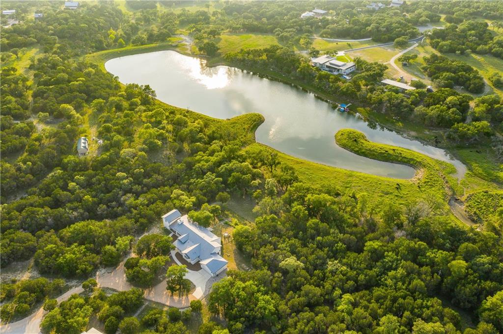 A private retreat nestled lakeside in the prestigious and highly desirable Mustang Valley subdivision.  A winding driveway opens up to the single story Hill Country home overlooking the private Comanche Lake and gorgeous trees.  A deep wrap around porch stretches across the back of the home so you can watch the sunrise over the water and enjoy the sounds of the morning coming alive.  The property goes out into the lake and owns part of the land jutting out into the water.  You can fish, swim and canoe from your own private oasis.  The home has extensive upgrades including a gourmet kitchen with granite counter tops, built in refrigerator, extensive custom cabinetry and wine fridge.  The living room has a gas log fireplace, tall wood beamed ceilings, and huge windows looking over the lake.  Total of 3 full bedrooms and 3 and 1/2 baths with two offices. One office could be a 3rd bedroom in main house.  Attached casita has a living area, kitchenette, loft and full bath. The home is serviced with a 25,000 gallon Rain Water Collection system (upgraded and serviced 2021) and the heating and cooling is a recently installed geothermal system. The attic has spray foam insulation and the home is extremely energy efficient. 1500 square foot metal shop with water and power and large 14x10 roll up door for RV storage.  Shop has plug in for RV storage or power for shop.  Low taxes, Wimberley ISD, minutes to HEB, shopping and great community amenities. Internet options with Anvilcom and HughestNet.  The property is accessed from Fischer Store Road with a private entrance. Cattle guard to be removed prior to closing. You will never want to leave once you set foot on your own private Hill Country lakeside resort.